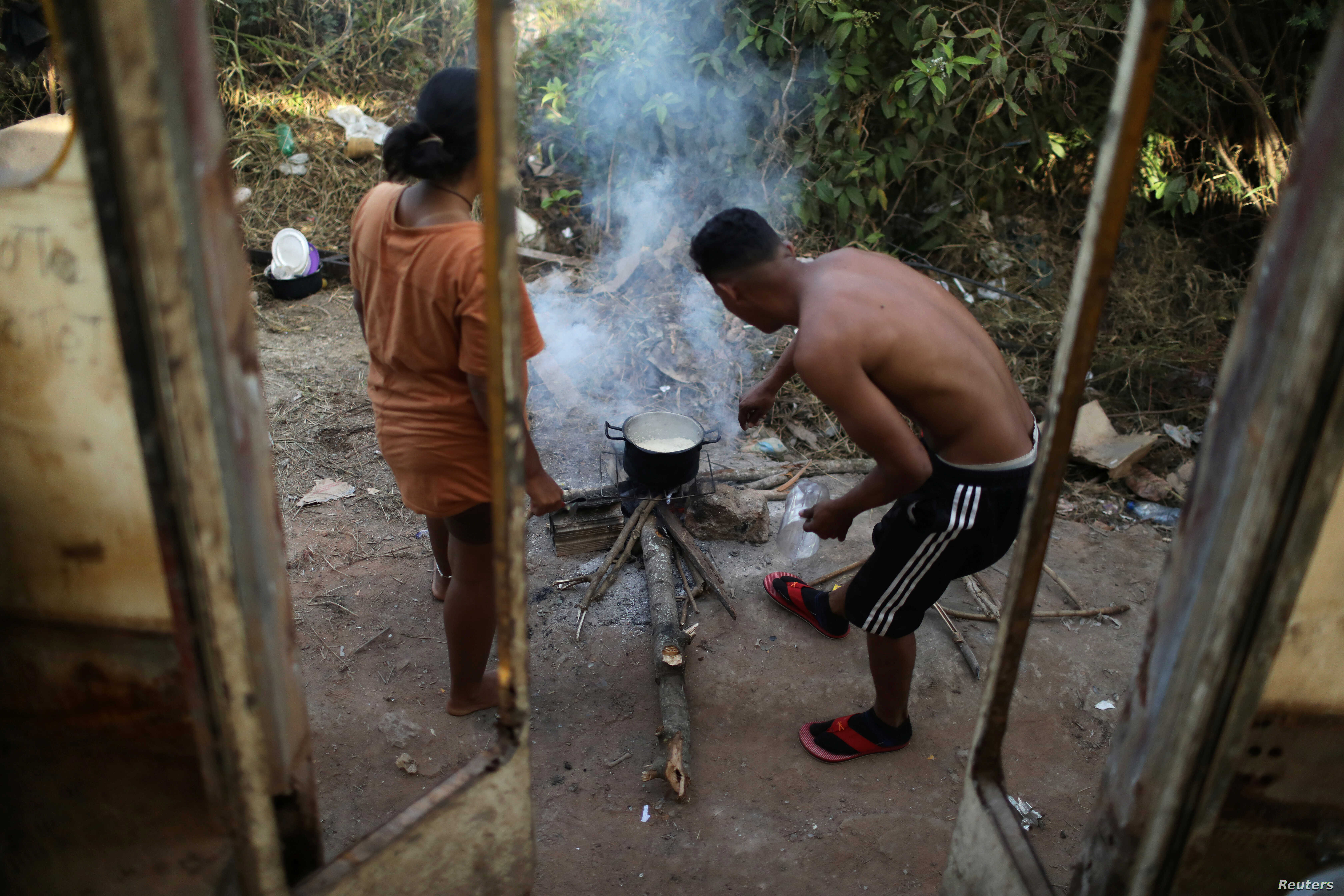 Venezuelans Hildemaro Ortiz and Ixora Sanguino cook outside of an abandoned bus in the border city of Pacaraima, Brazil, April 13, 2019.