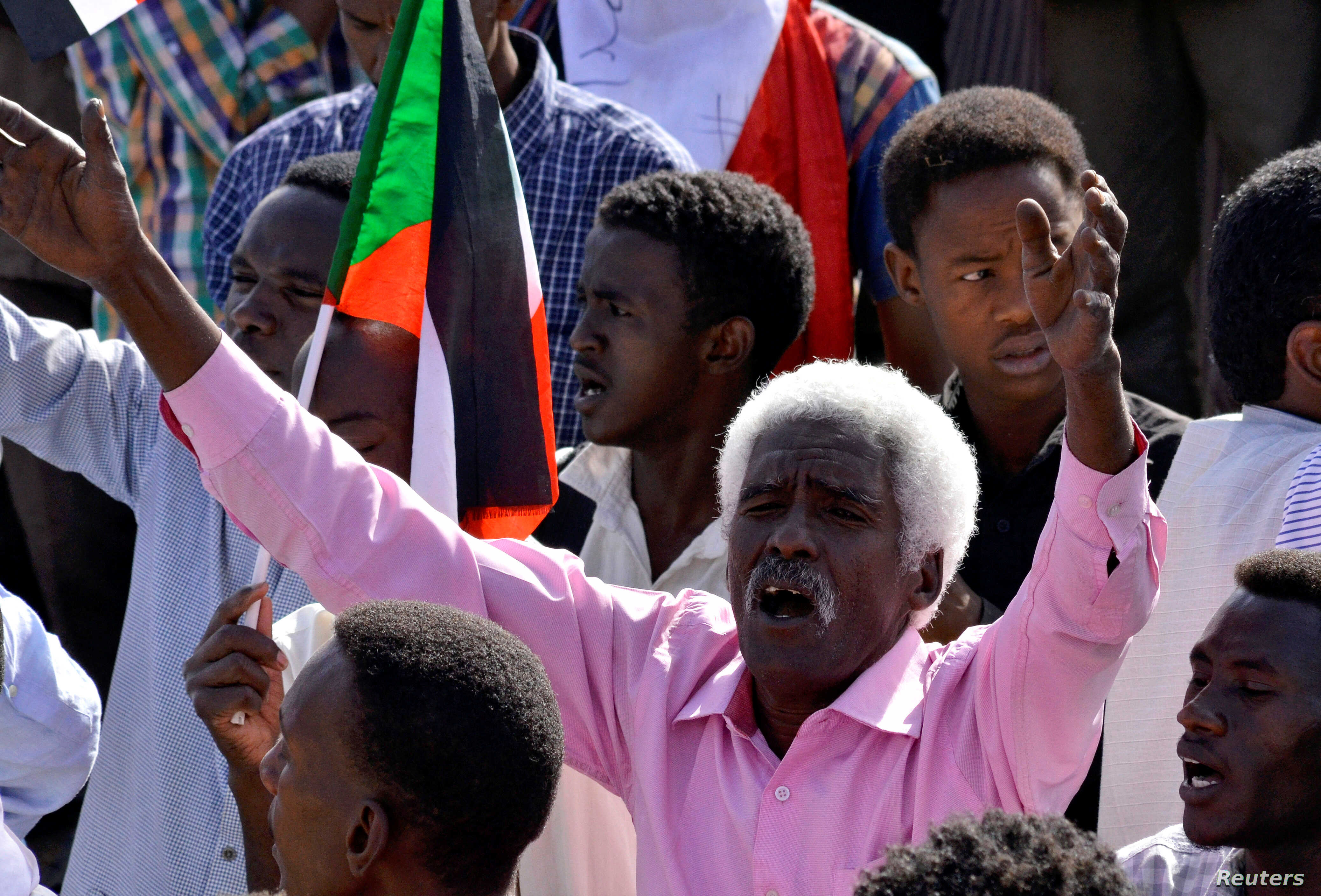A Sudanese demonstrator celebrates after Defense Minister Awad Ibn Auf stepped down as head of the country's transitional ruling military council, near the Defense Ministry in Khartoum, Sudan, April 13, 2019.