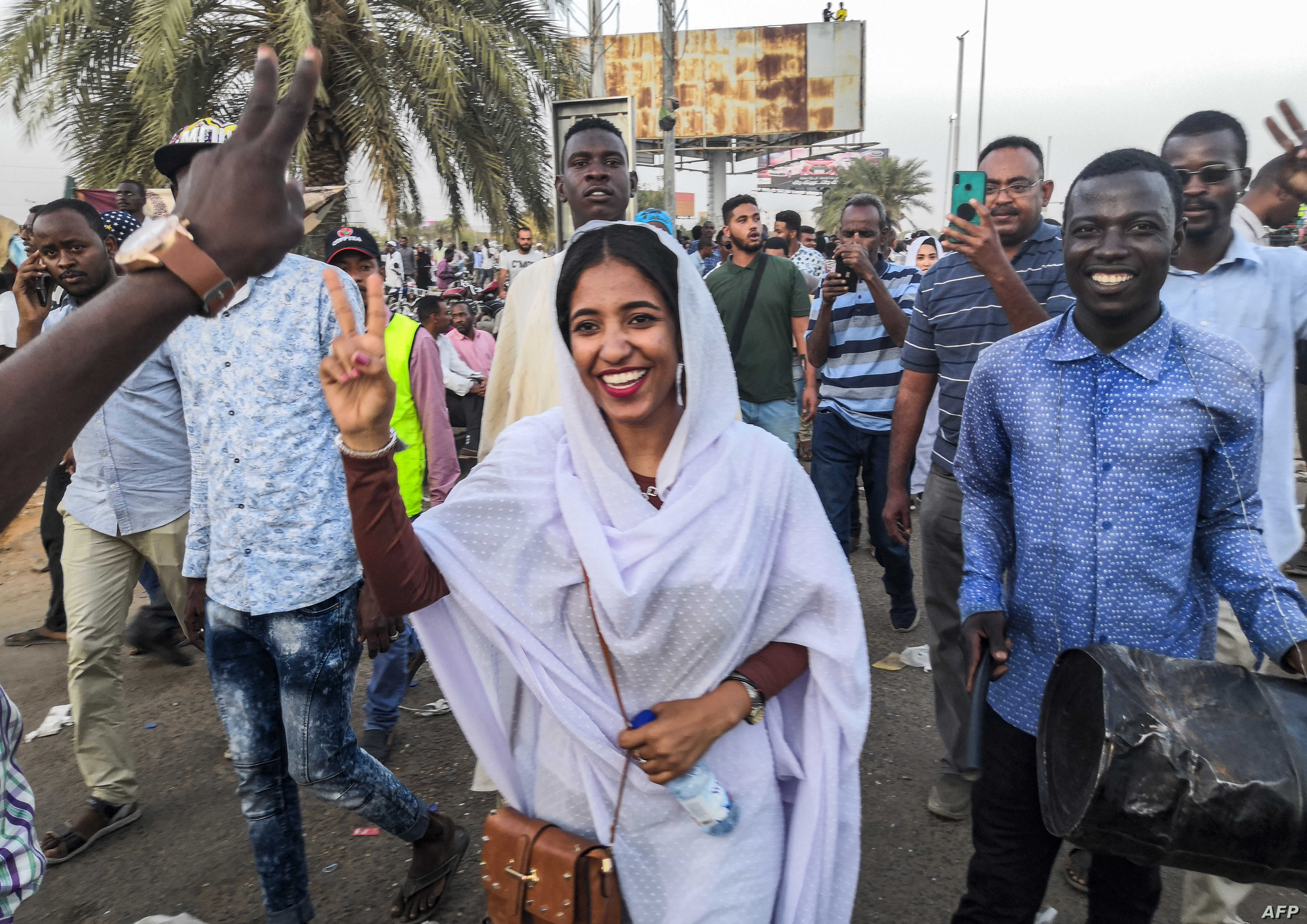 FILE - Alaa Salah, a Sudanese woman propelled to internet fame earlier this week after clips went viral of her leading powerful protest chants against President Omar al-Bashir, flashes the victory gesture and shouts slogans while marching during a de...