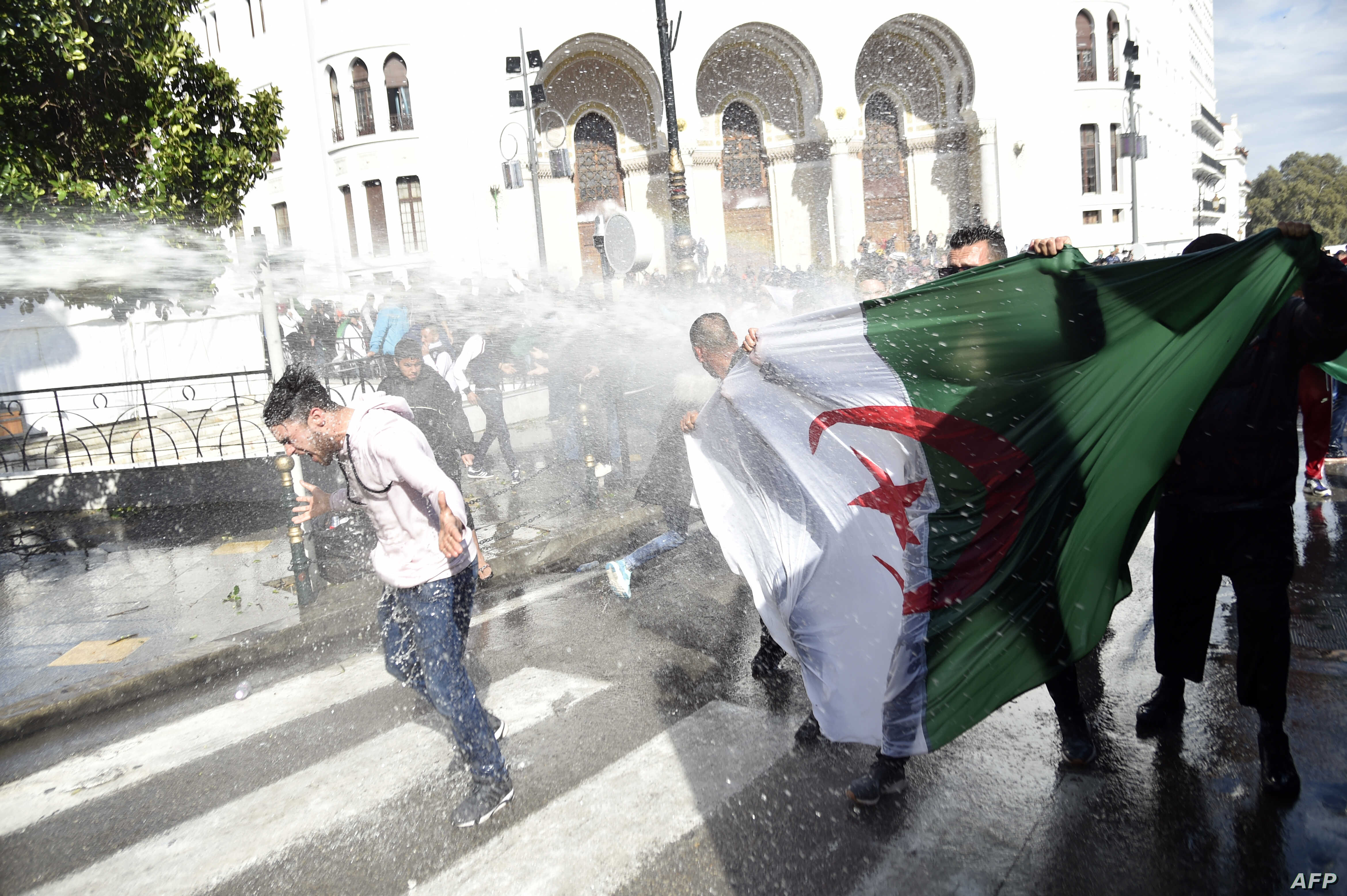 Algerian riot police spray anti-government protesters with water during a demonstration in the capital Algiers, April 9, 2019