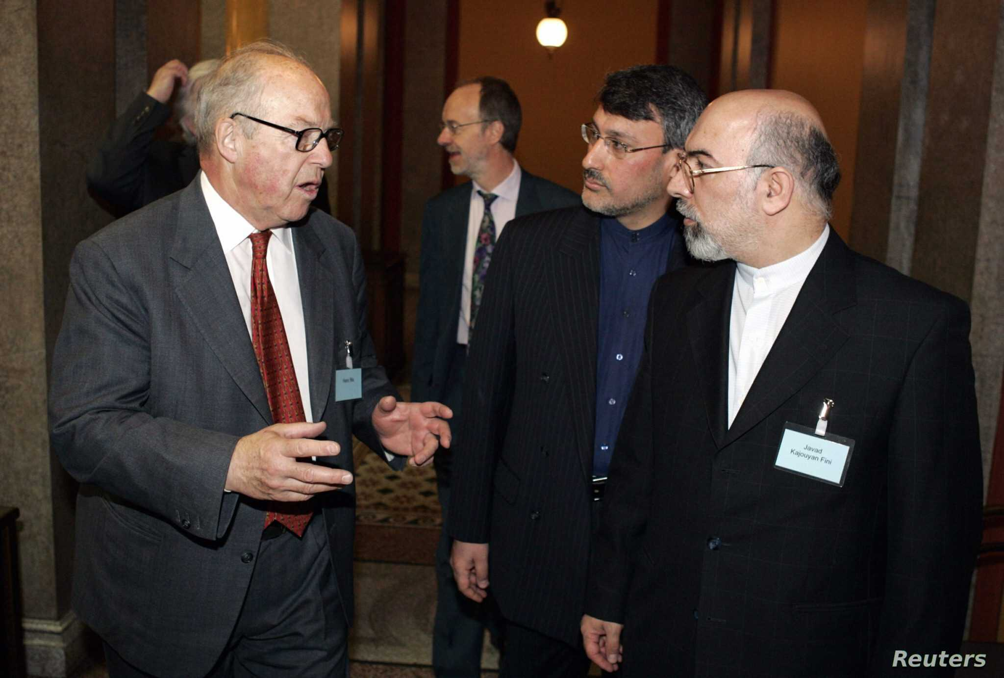 Iran's Ambassador to Finland Javad Kajoyan Fini and the Director of the Ministry of Foreign Affairs of Iran Hamid Baeidinejad (second from right) talk to the former chief U.N. Weapons inspector Hans Blix in Helsinki, April 7, 2005..