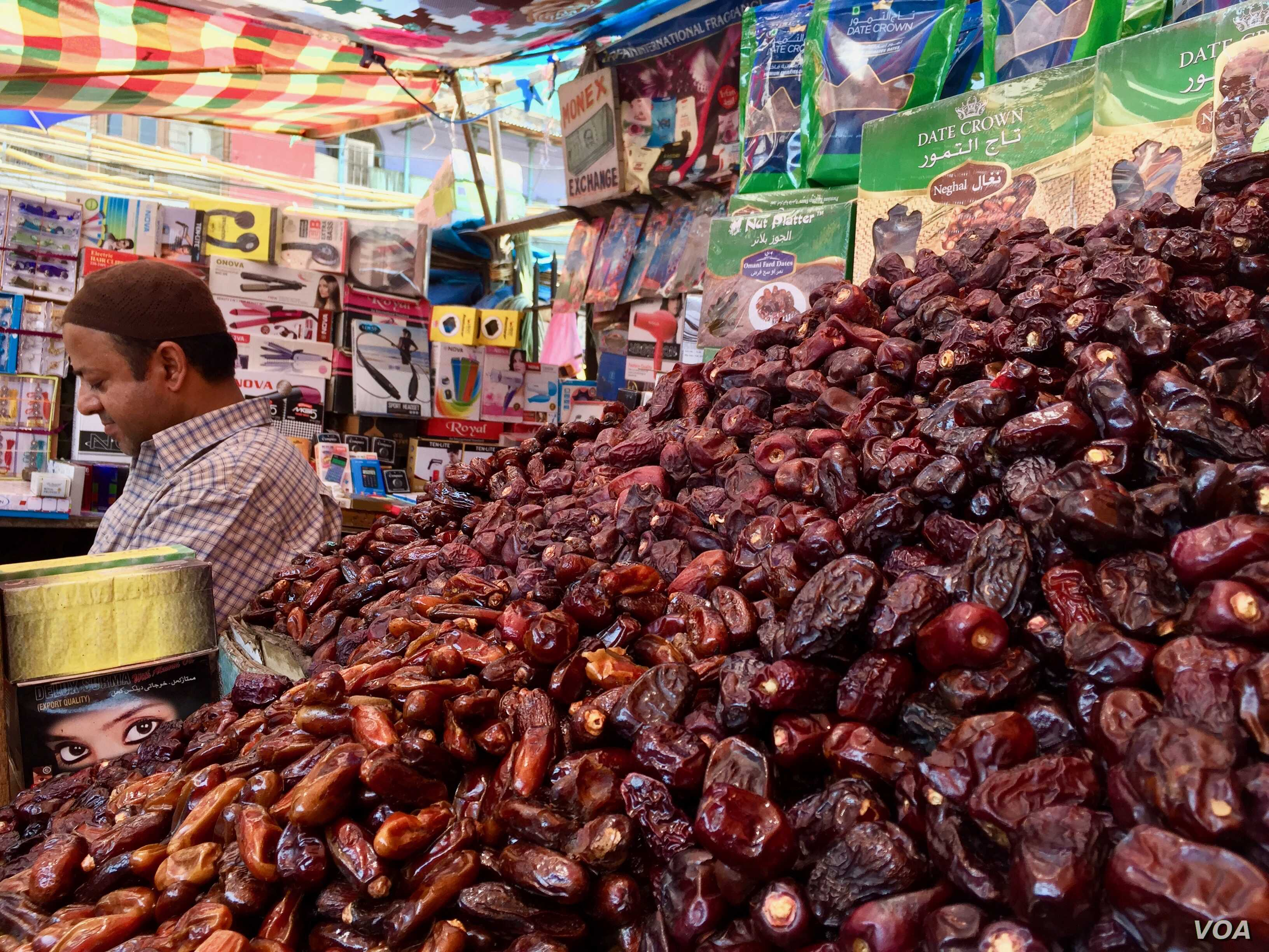 Vendor selling dates and traditional food items at a market in a Muslim dominated neighborhood in Delhi.