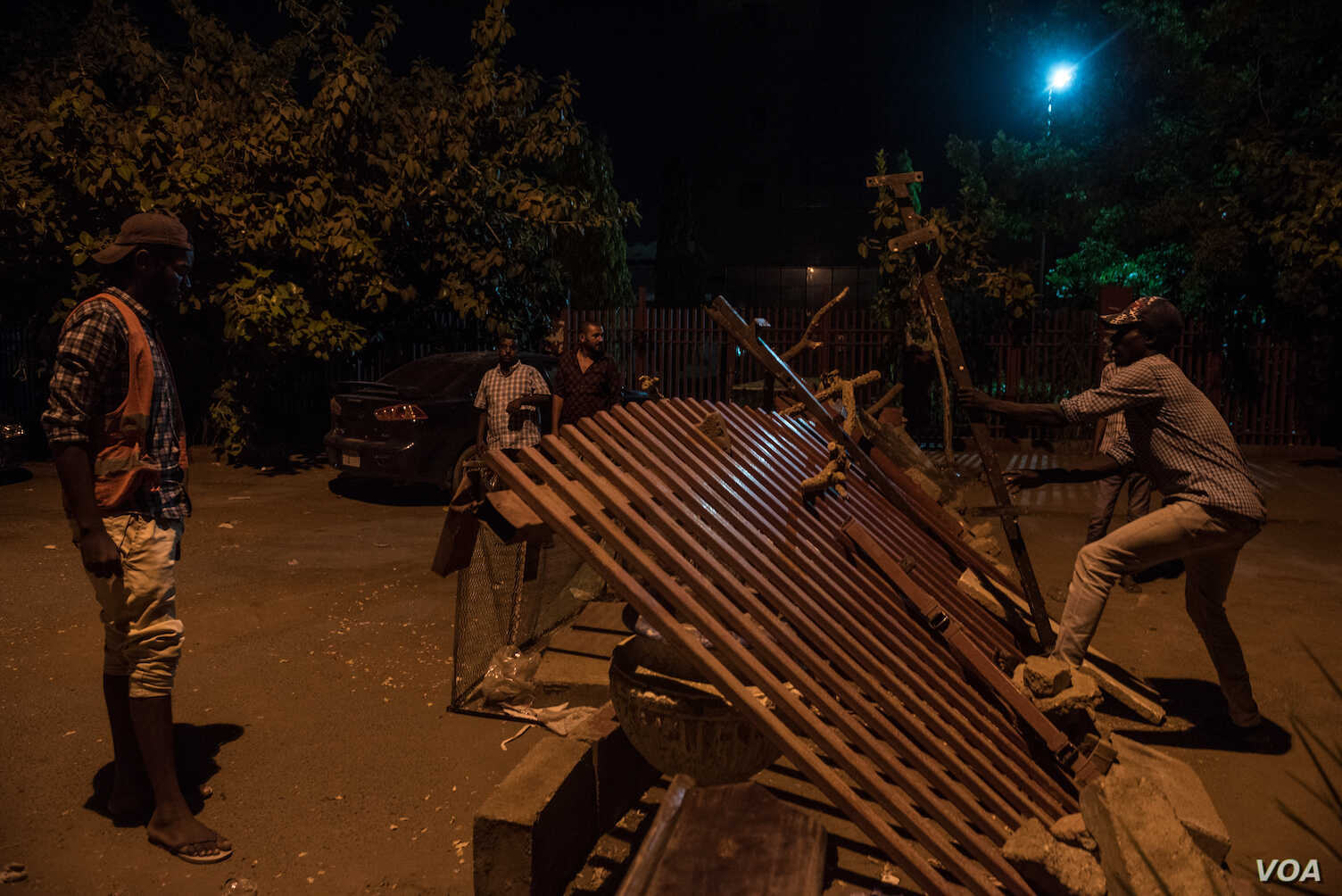 Protesters rebuild a barricade that was destroyed by a military vehicle at a Khartoum checkpoint on April 29, 2019. (J. Patinkin for VOA)