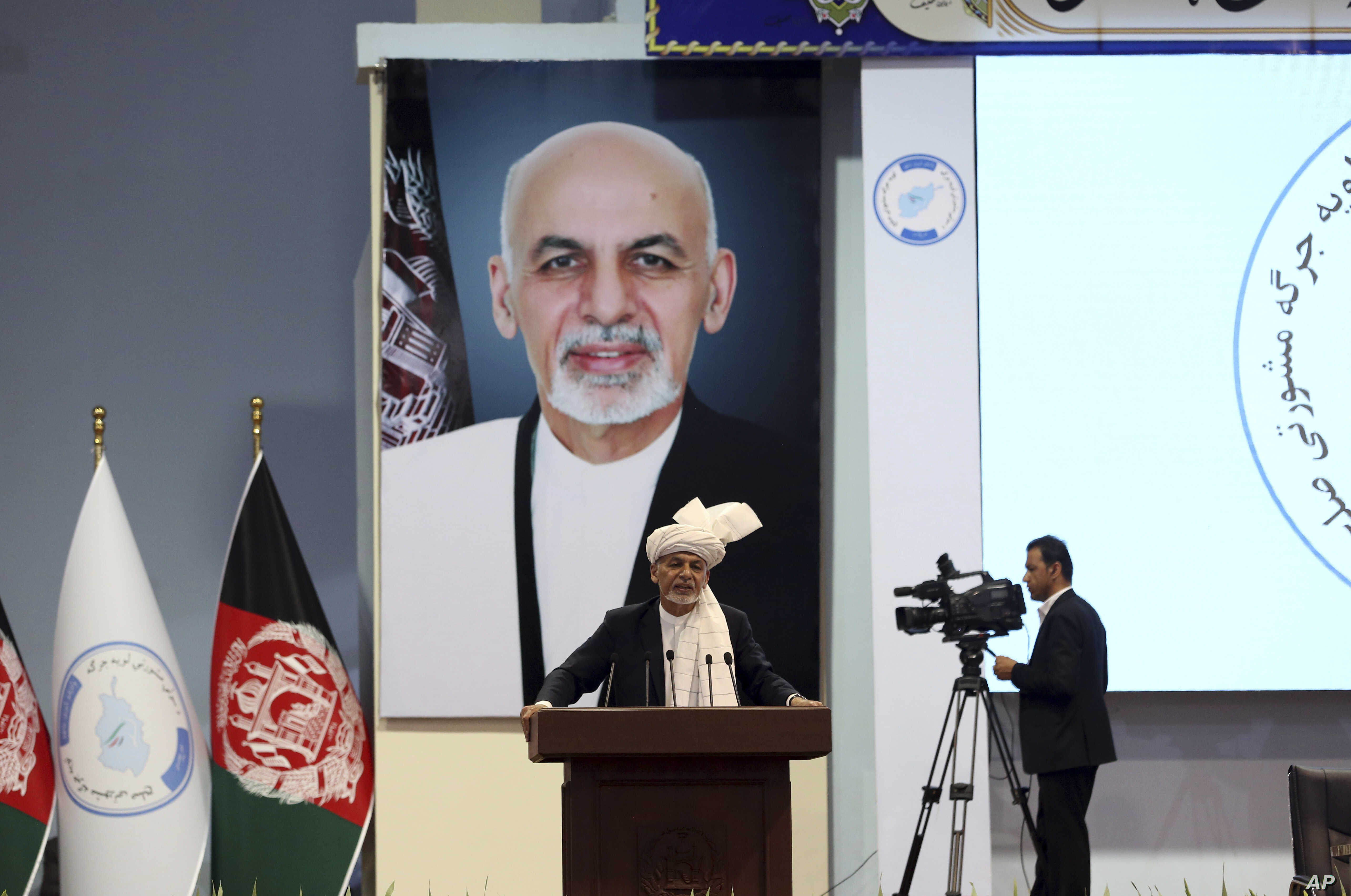 Backdropped by his own image, Afghan President Ashraf Ghani speaks to delegates during the first day of the Afghan Loya Jirga meeting in Kabul, Afghanistan, April 29, 2019.