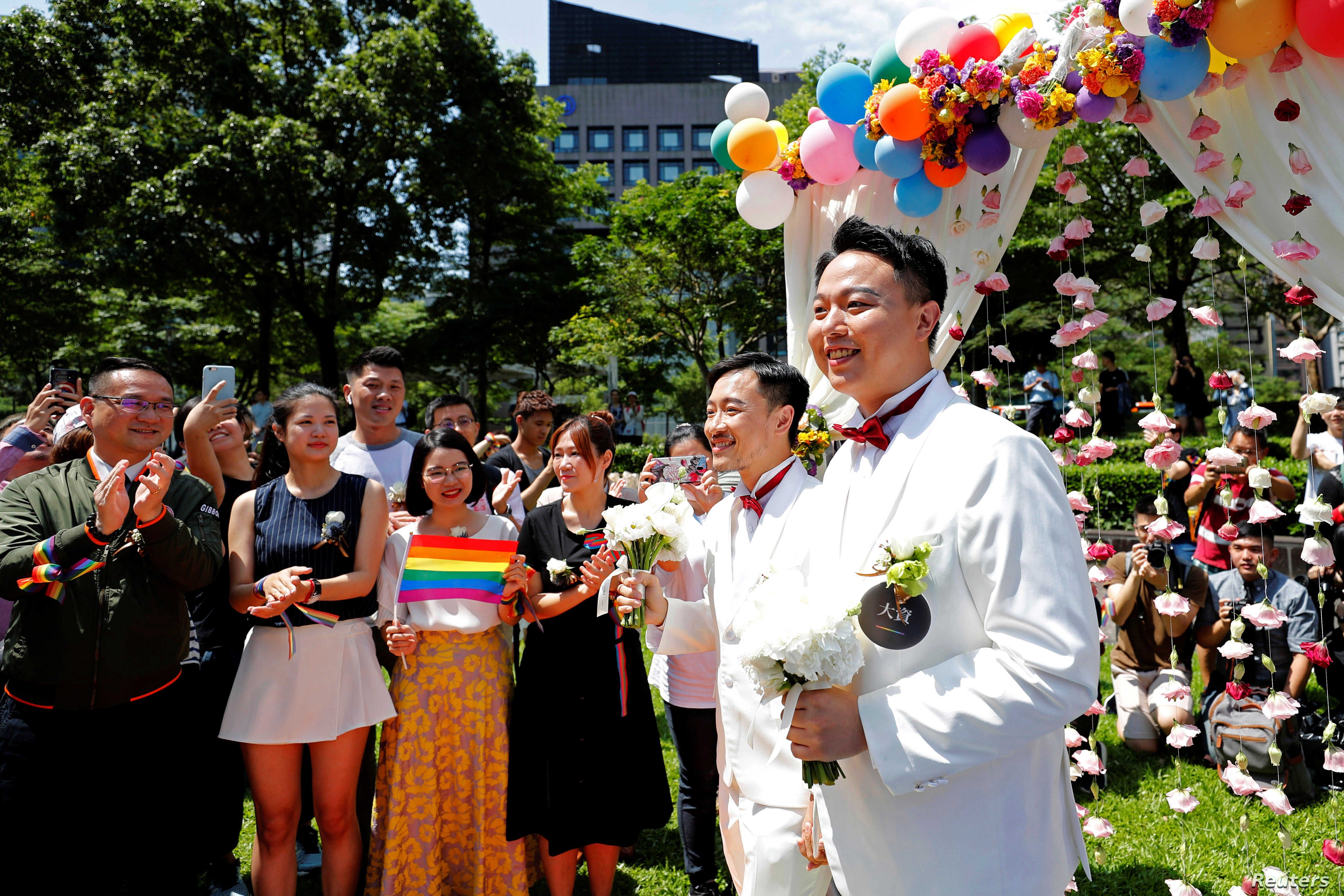 Gay newlyweds walk on a giant rainbow flag at a same-sex marriage party after registering their marriage in Taipei, Taiwan, May 24, 2019.