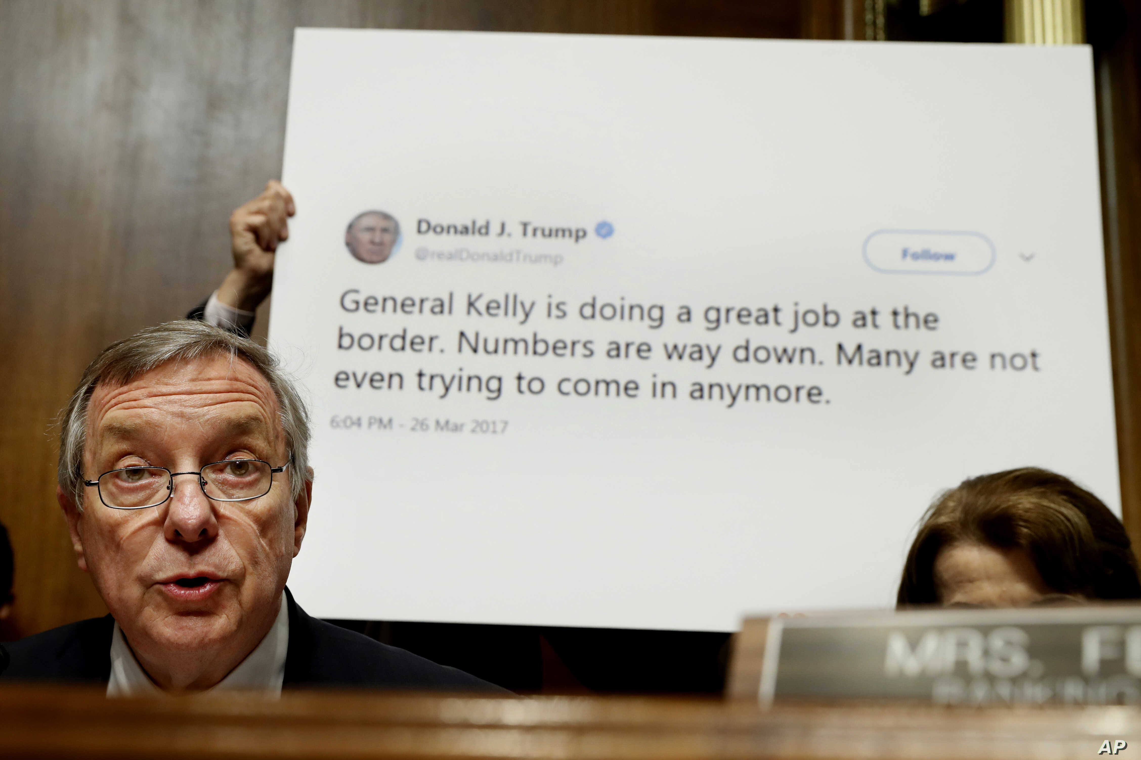 Sen. Dick Durbin, D-Ill., ranking Member of the Senate Committee on the Judiciary, Subcommittee on Border Security and Immigration, speaks while a staffer holds up a Twitter quote by President Donald Trump, during a subcommittee hearing about the bor...