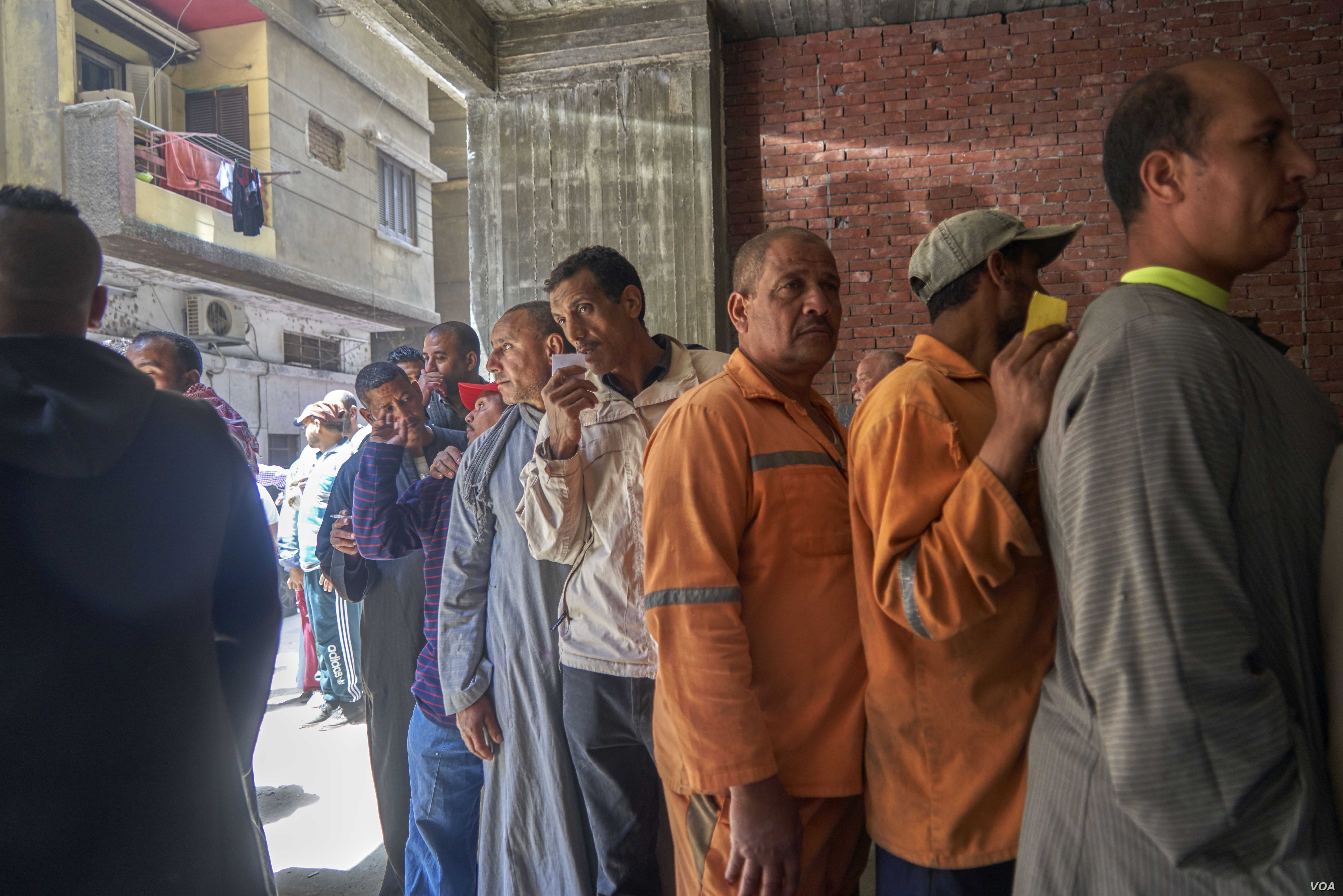 After voting, these men wait in line for bags of food or a small amount of money in Cairo on April 20, 2019.