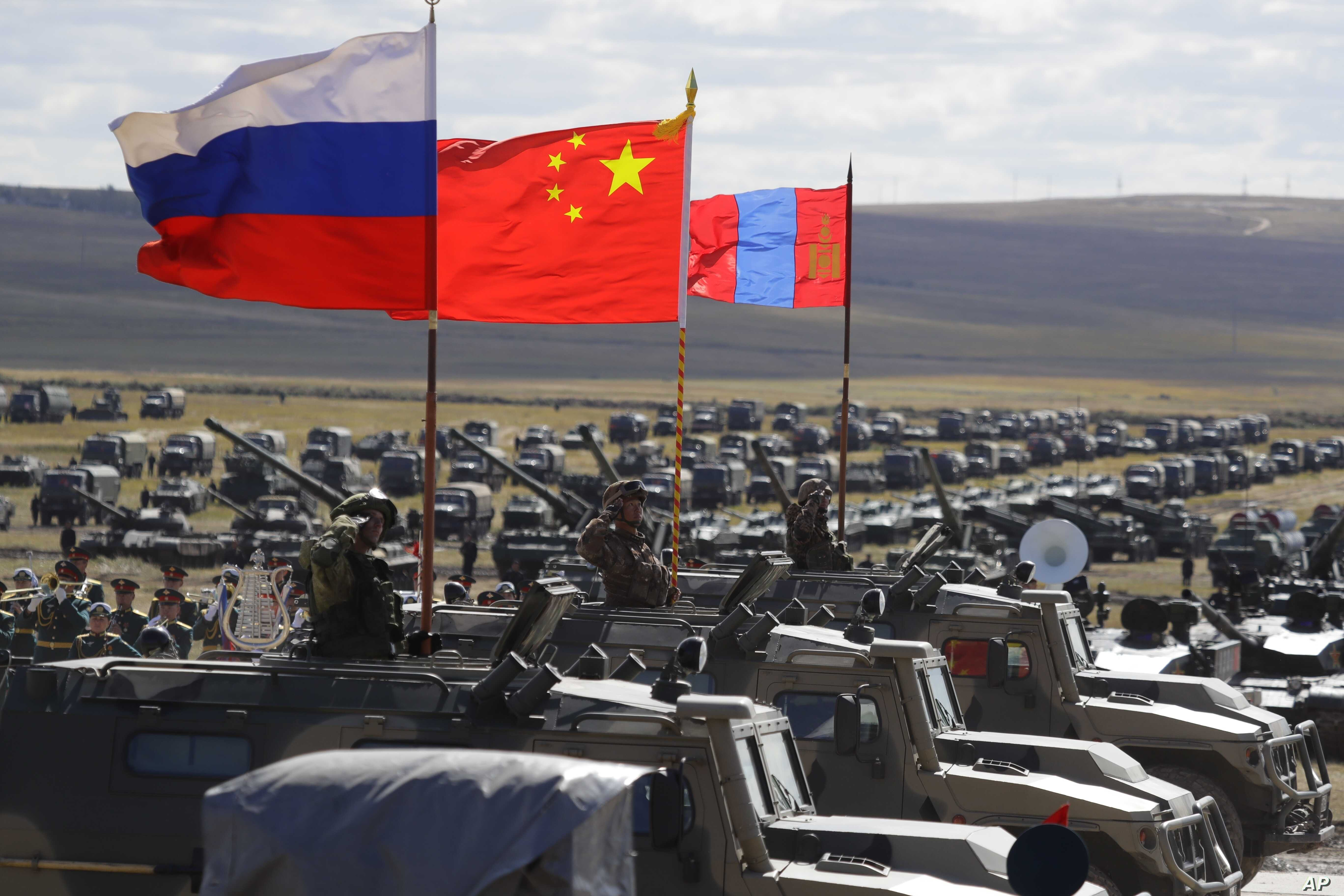 """FILE - Russian, Chinese and Mongolian national flags set on armored vehicles develop in the wind during a military exercises on training ground """"Tsugol, south-east of the city of Chita during the military exercises Vostok 2018 in Eastern Siberia, Rus..."""