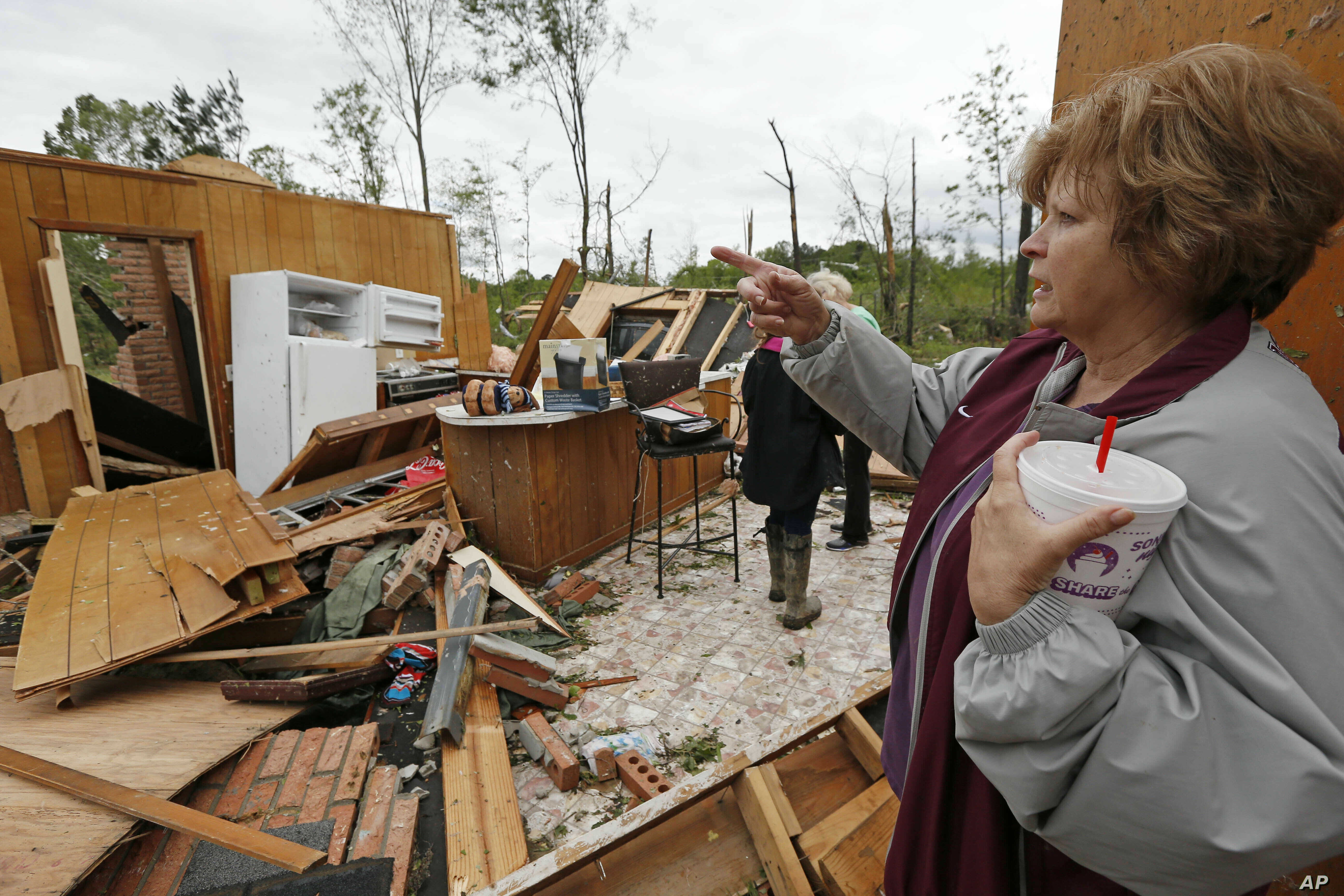 Freda Jenkins looks around the remains of a friend's damaged home, possibly by a tornado, April 19, 2019, in Morton, Miss.