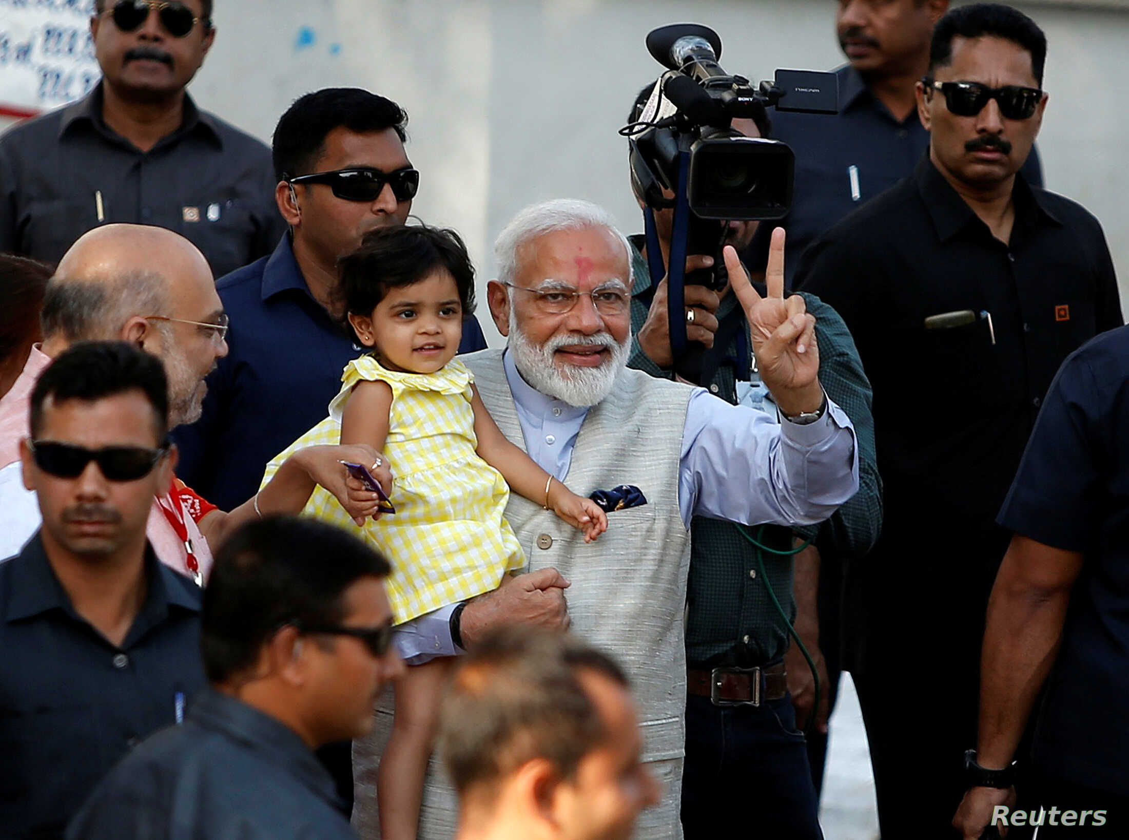 India's PM Minister Narendra Modi gestures as he holds the granddaughter of India's ruling Bharatiya Janata Party (BJP) president Amit Shah after he arrives to cast his vote at a polling station in Ahmedabad, Apr. 23, 2019.