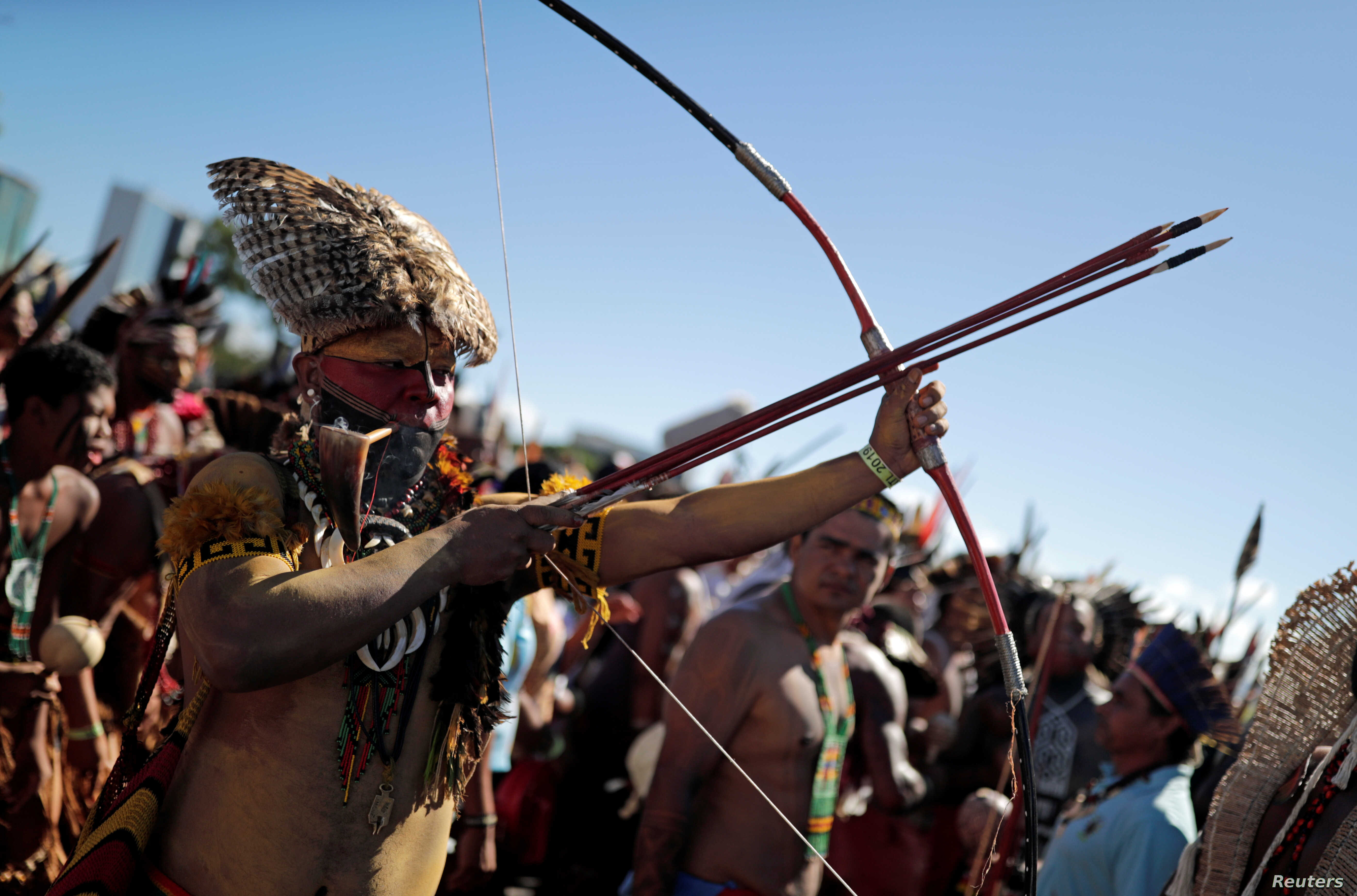 A member of an indigenous tribe holds a bow and arrows during a protest to defend land and cultural rights that indigenous people say are threatened by the government of Brazil's President Jair Bolsonaro, in Brasilia, April 26,