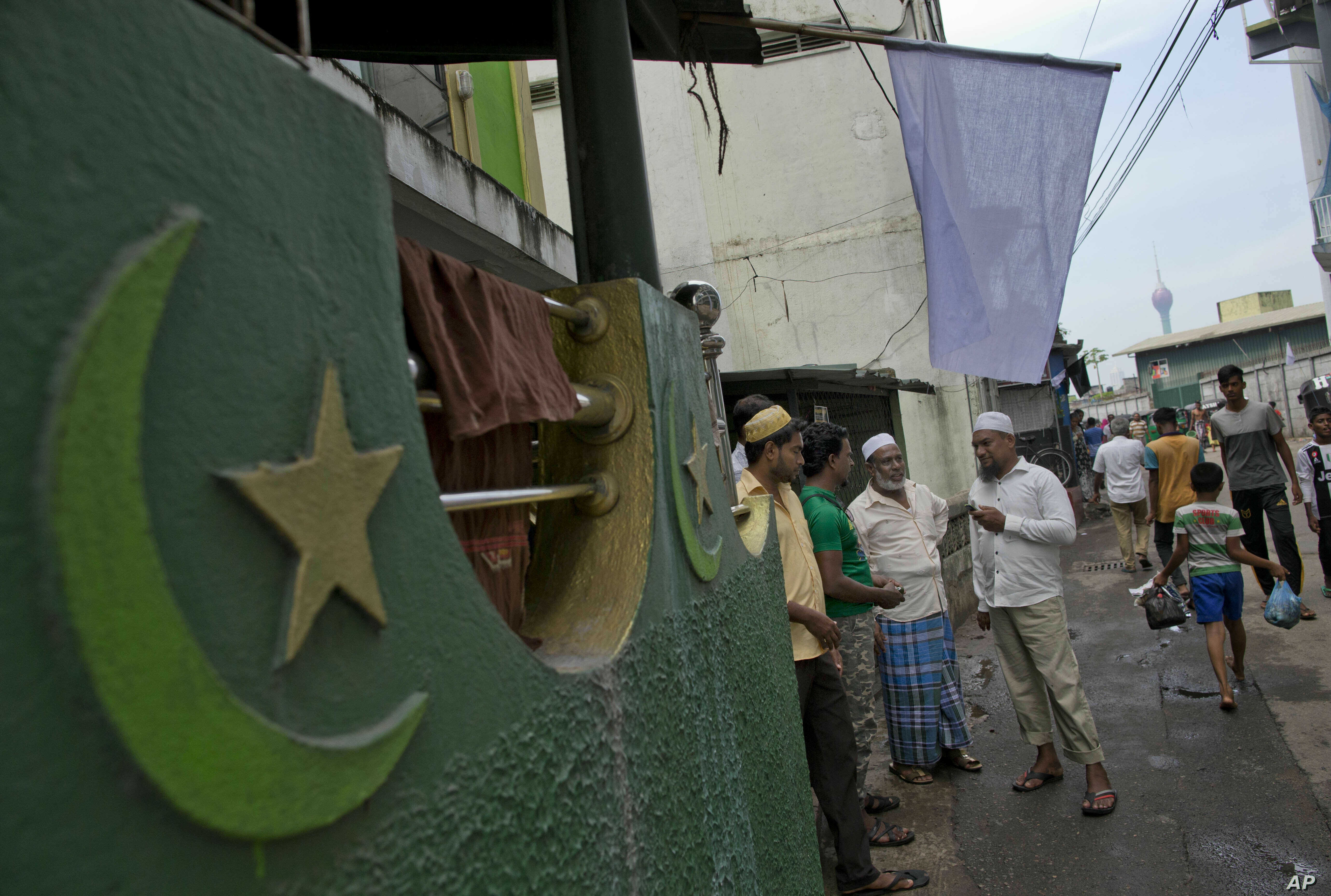Muslim men gather outside a mosque in Colombo, Sri Lanka, April 26, 2019. Sri Lanka's president has appealed to the island nation not to view its minority Muslim community as terrorists in the wake of Easter attacks that officials say were carried ...