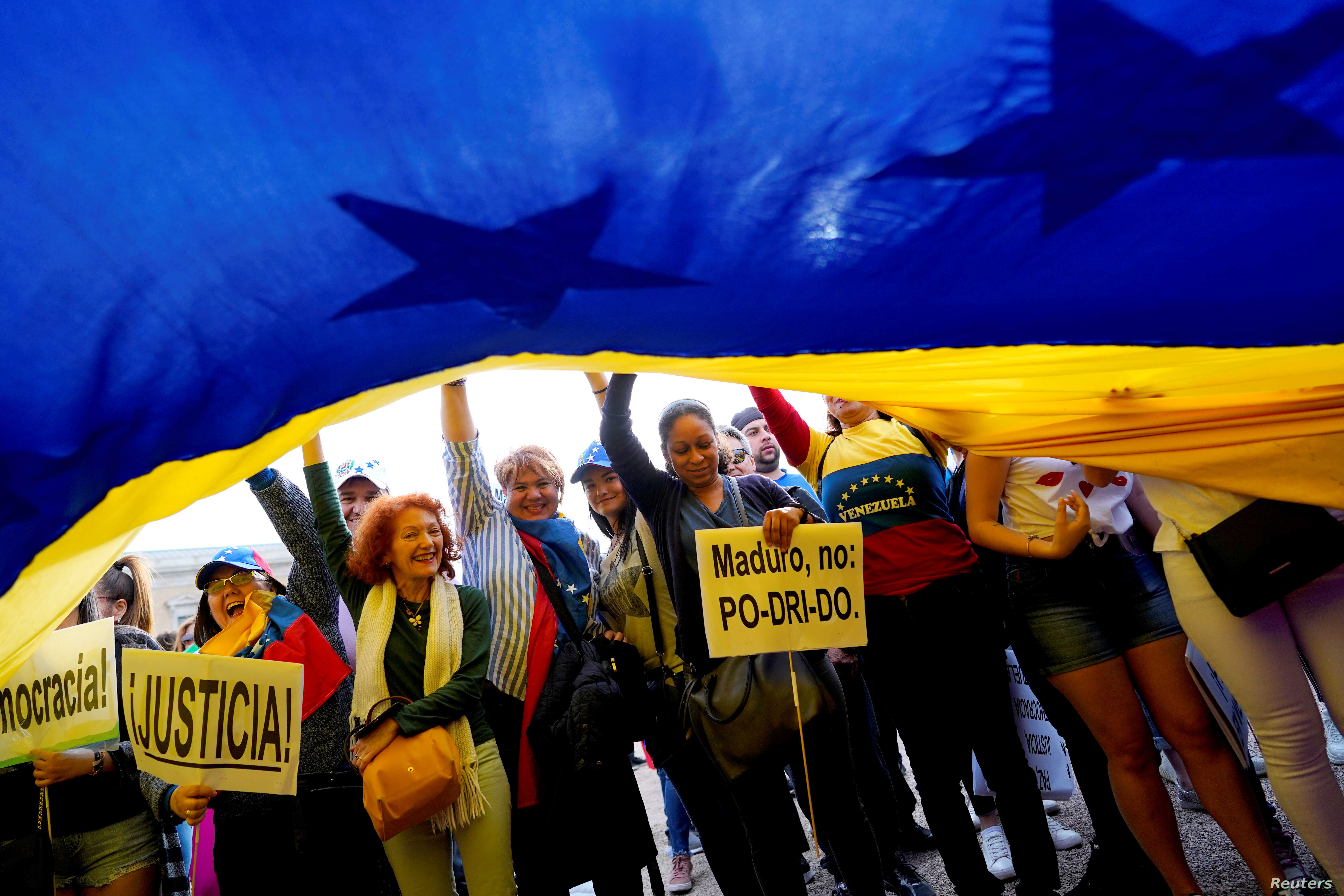 People reacts as they wave a Venezuelan flag during a protest in support of Venezuelan opposition leader Juan Guaido at Colon Square in Madrid, Spain, May 1, 2019.