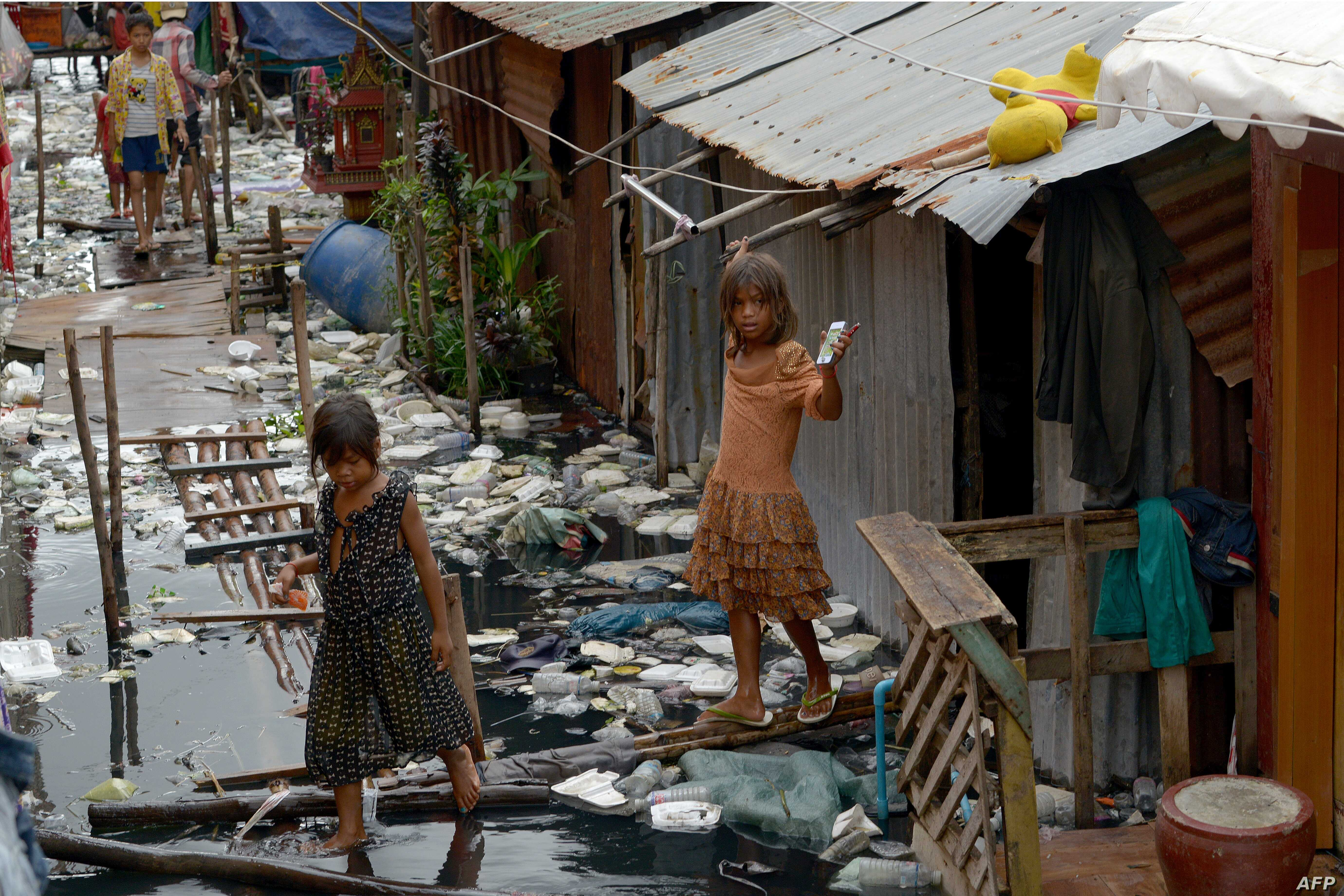 FILE - Cambodian children wade in polluted water at a village in Phnom Penh, Oct. 18, 2017.