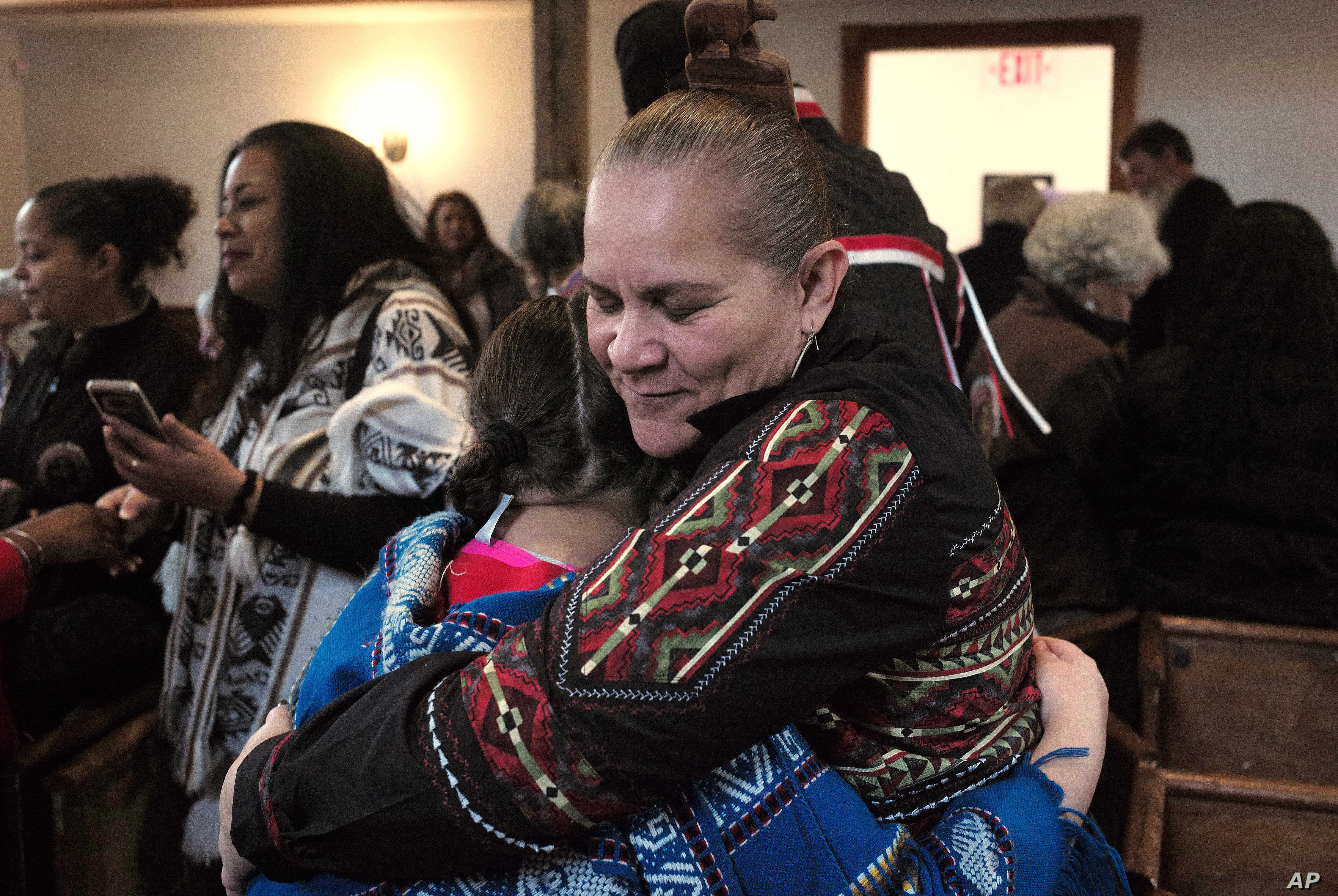 """Jessie """"Little Doe"""" Baird (R) hugs a member of the audience following celebration at the Old Indian Meeting House, in Mashpee, Mass., Nov. 18, 2017.  Baird and other linguists are working reclaim the language of the Wampanoags, the tribe that helped ..."""