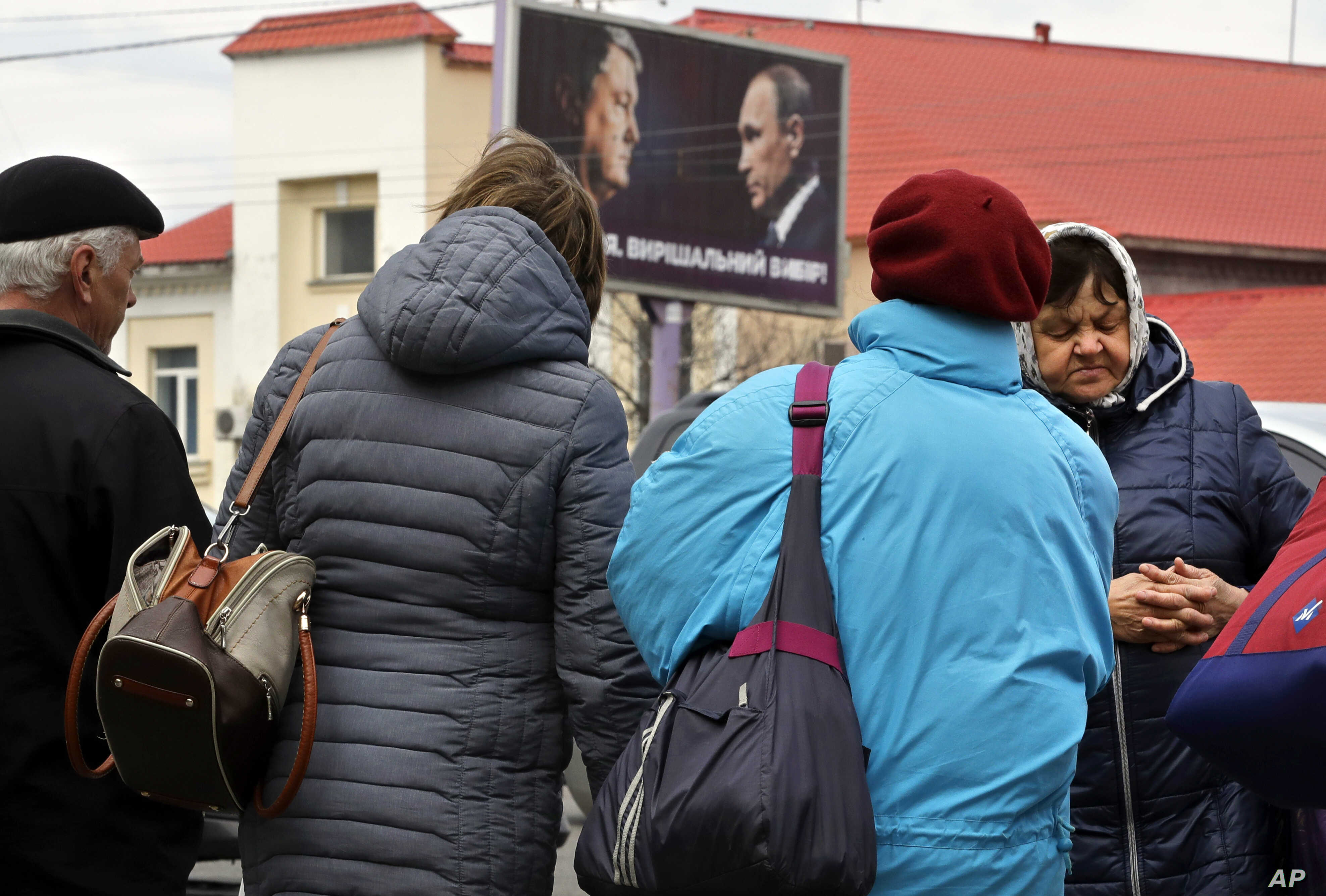 People stand on the street with a billboard depicting Ukraine's President Petro Poroshenko and Russian President Vladimir Putin looking at each other om the background, in Kyiv, Ukraine, April 17, 2019.