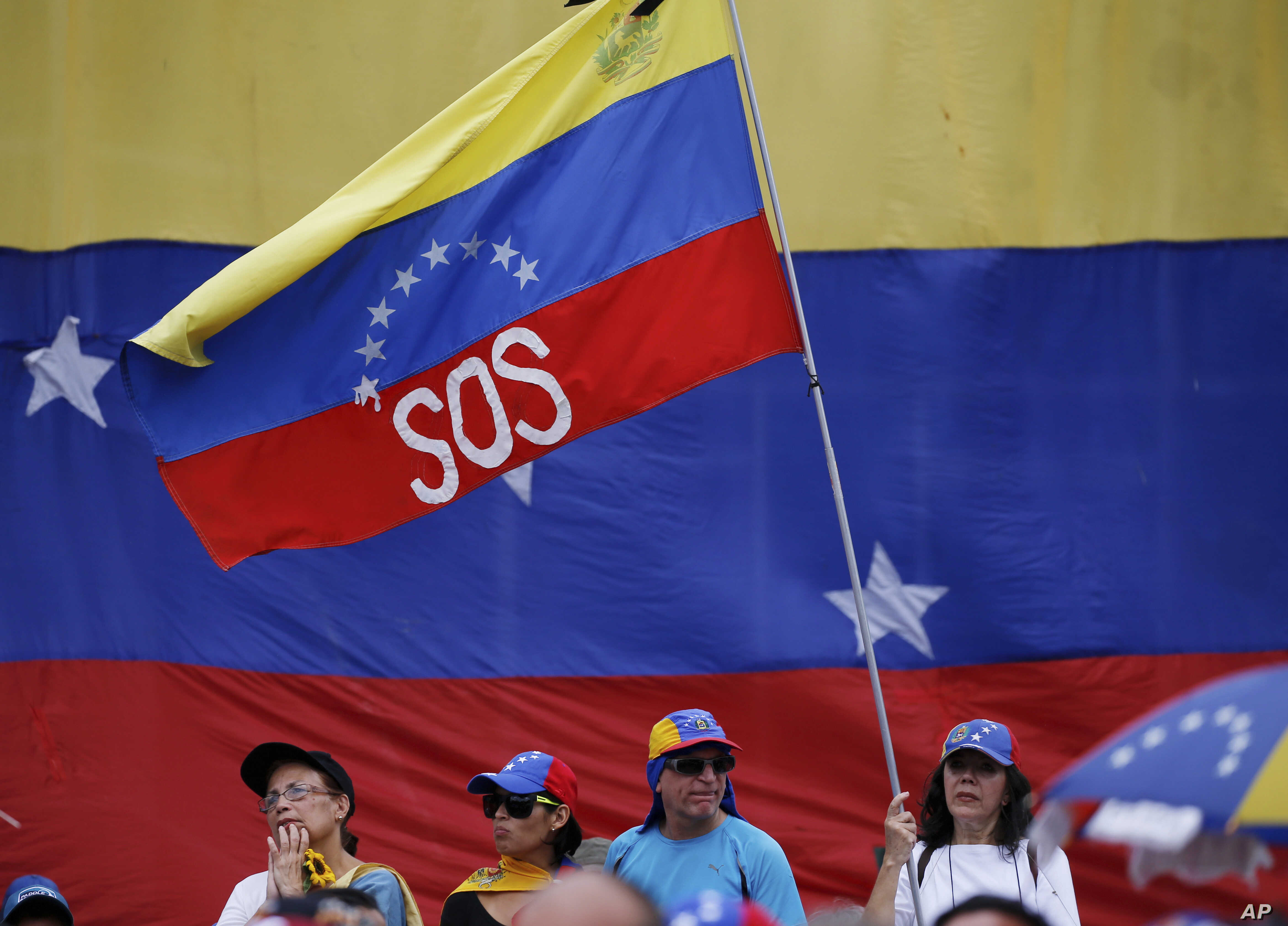 "A supporter of Venezuela's opposition leader and self-proclaimed interim president Juan Guaidó, waves a Venezuelan flag marked with the letters ""SOS"" during a rally in Caracas, Venezuela, May 11, 2019."