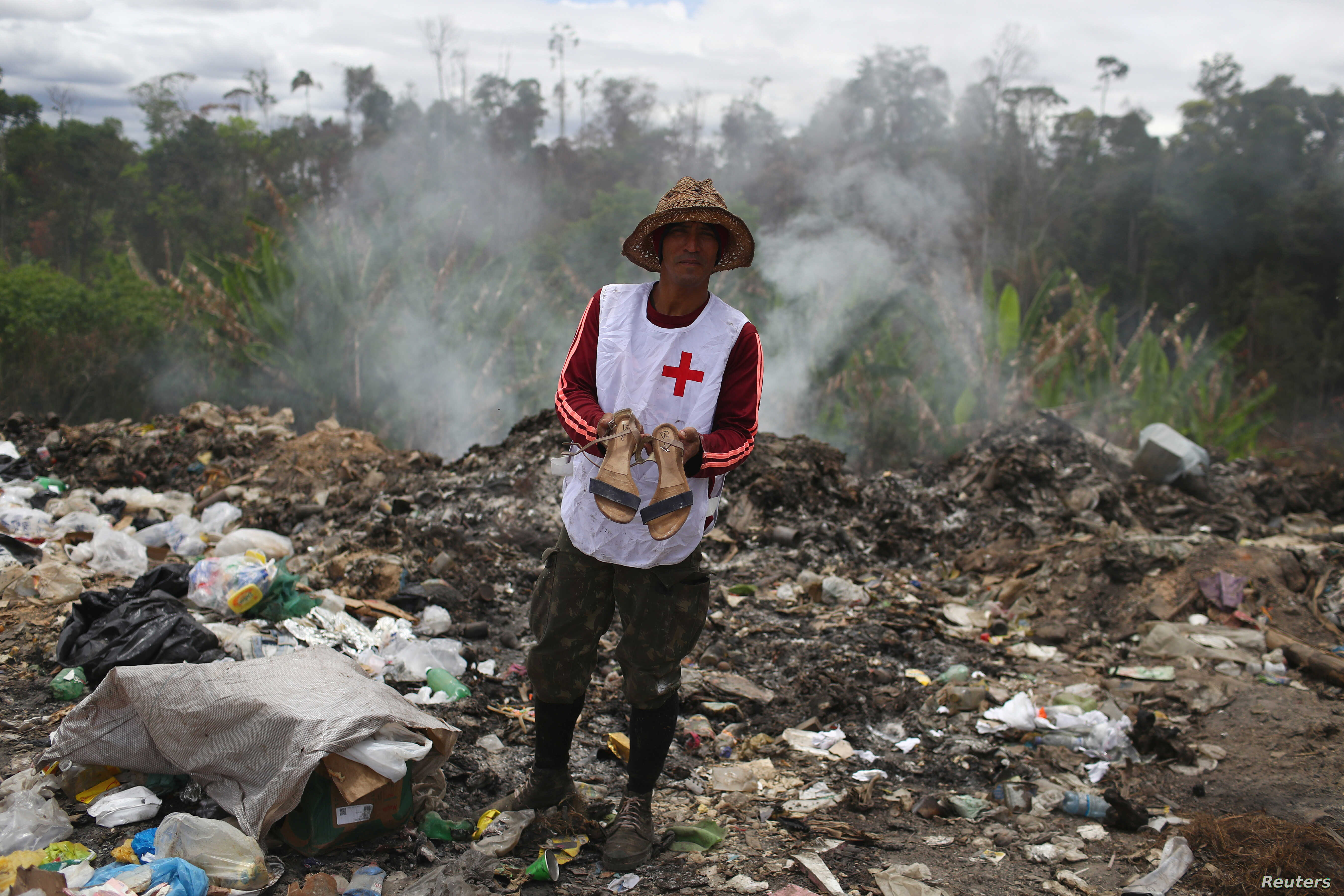 Venezuelan Charles Sanchez holds a pair of shoes after scraping on a garbage dump in the border city of Pacaraima, Brazil, April 15, 2019.