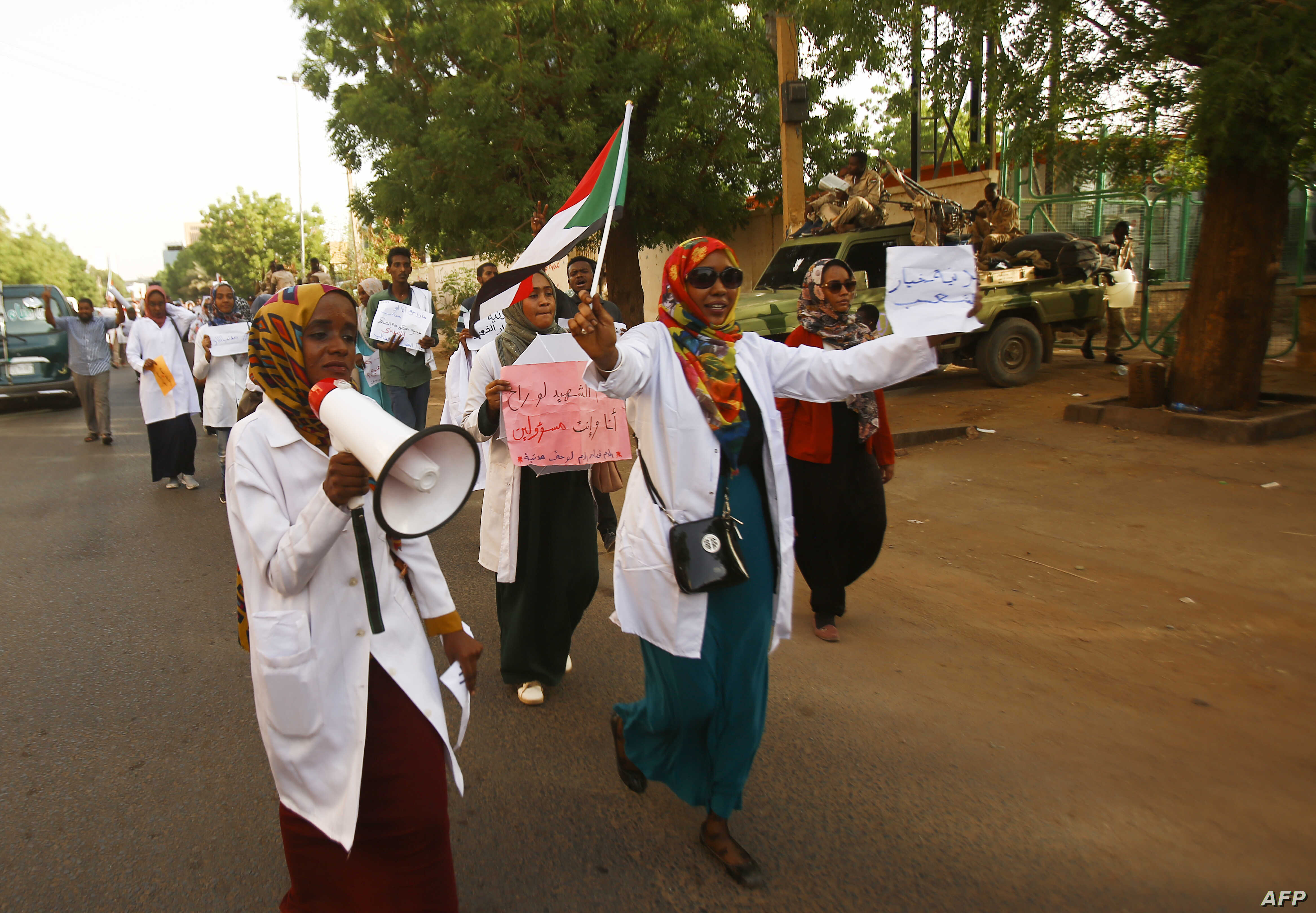 Sudanese medics shout slogans as they hold a rally in front of a hospital in the capital Khartoum on May 23, 2019.