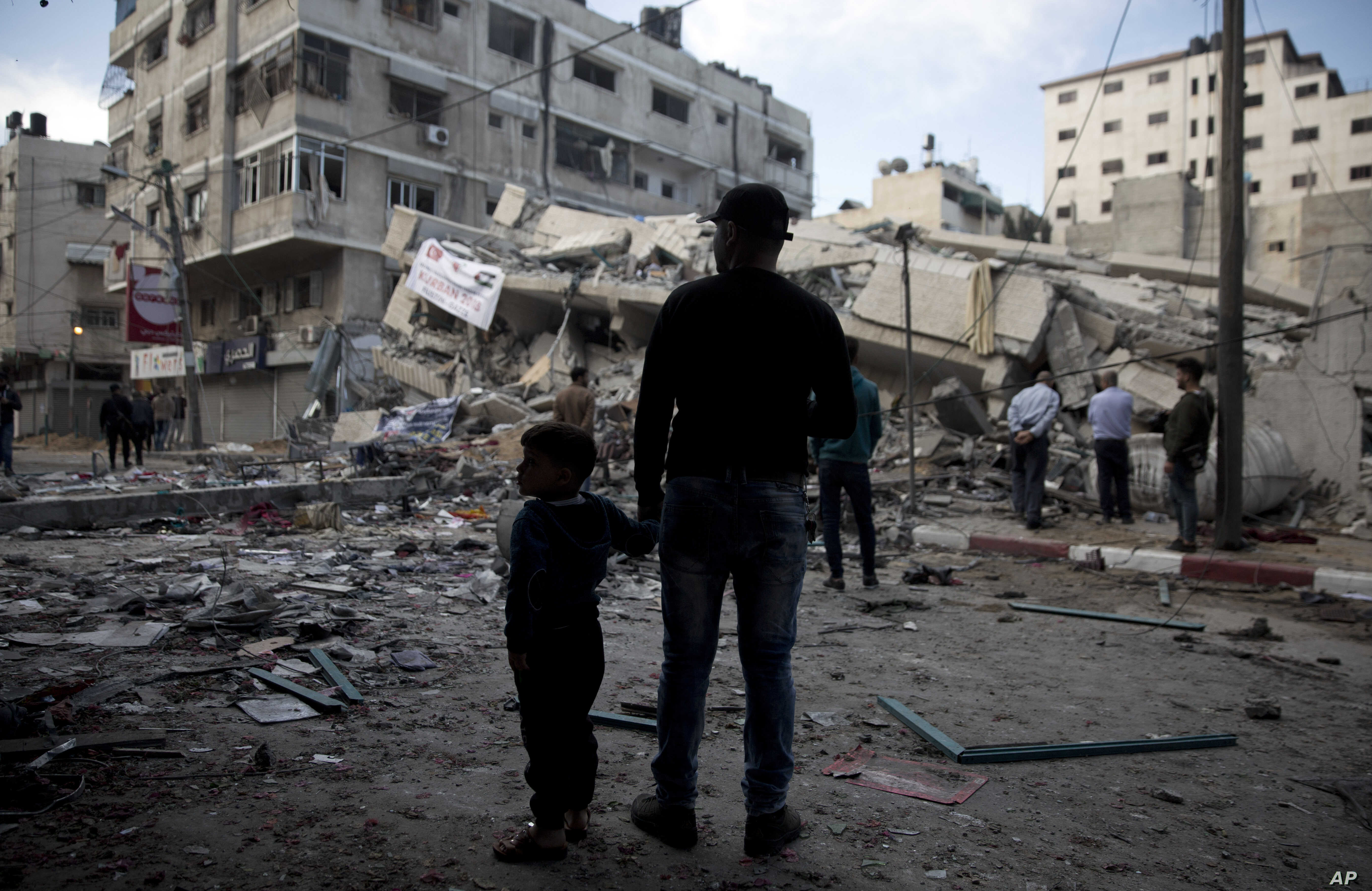 Palestinians stand in front of a destroyed multi-story building was hit by Israeli airstrikes in Gaza City, May 5, 2019.
