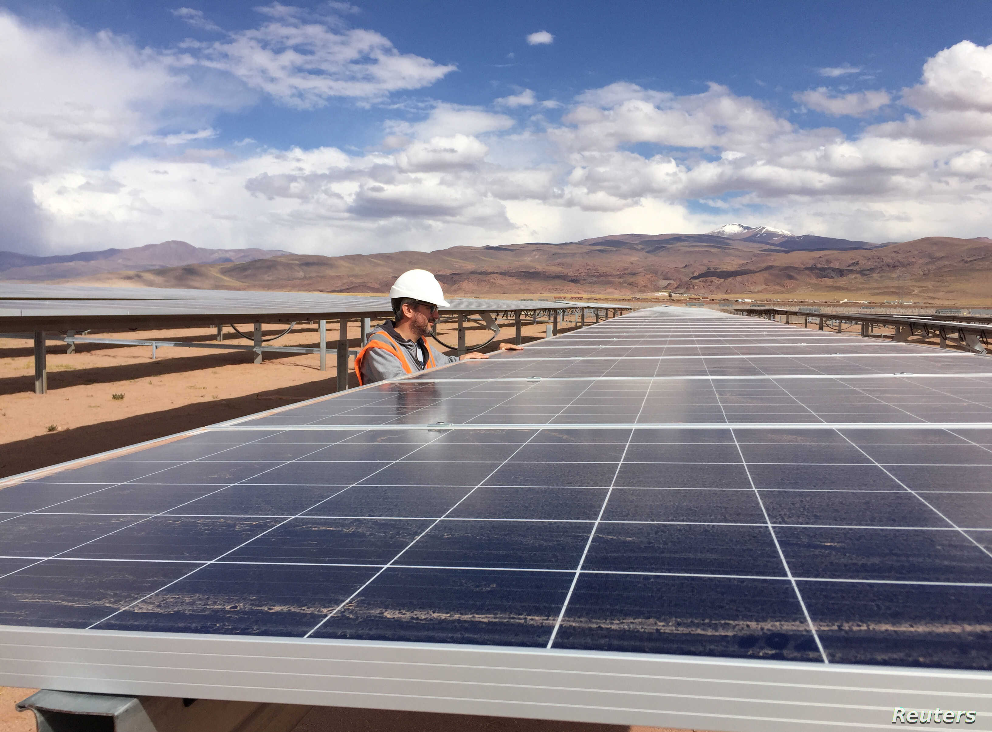 FILE - Guillermo Giralt, technical director of Cauchari Solar, stands next to solar panels at a solar farm, built on the back of funding and technology from China, in Salar de Cauchari, Argentina, April 3, 2019.