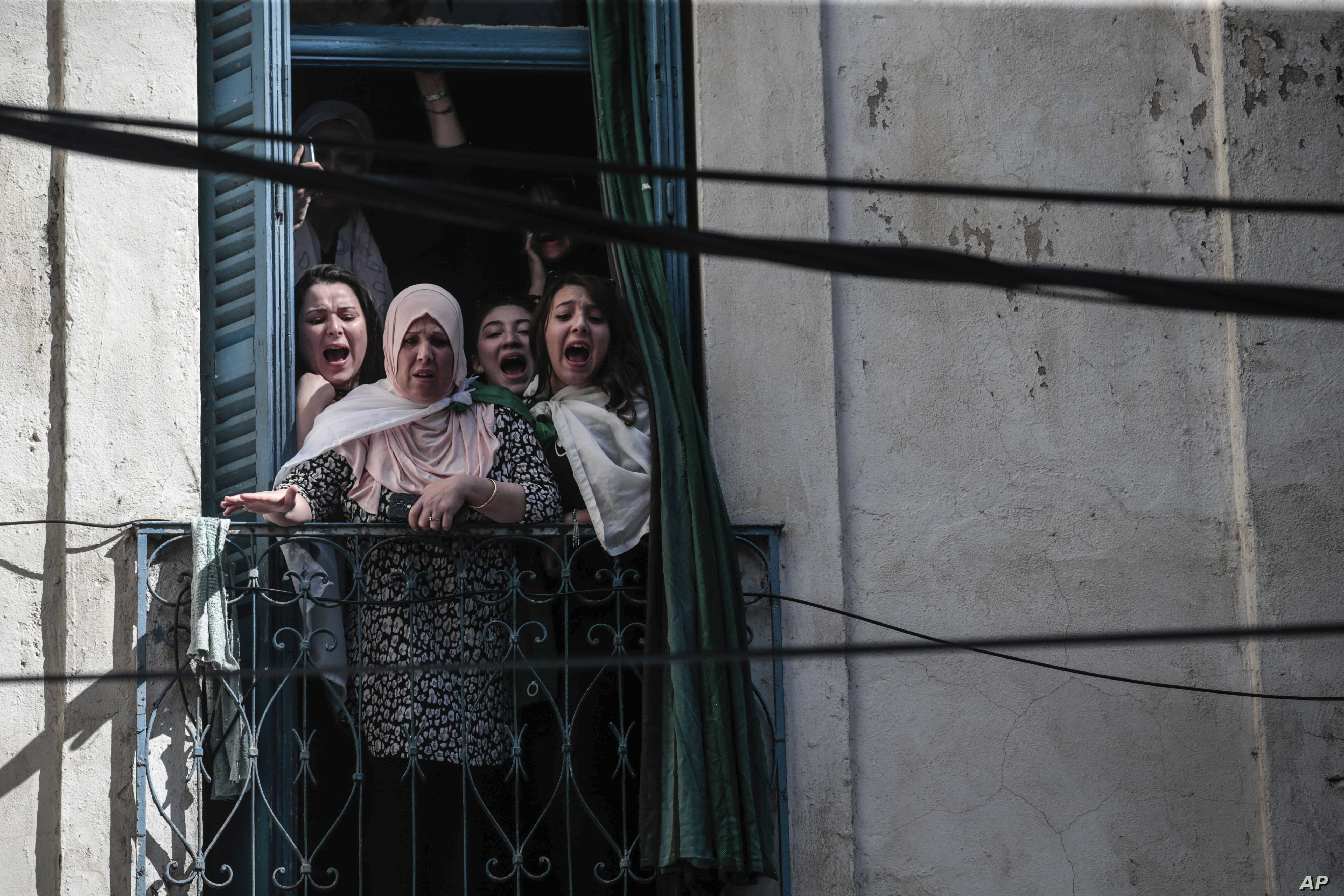 Women react from their balconies as police clash with protesters during a demonstration against the country's leadership, in Algiers,  April 12, 2019.