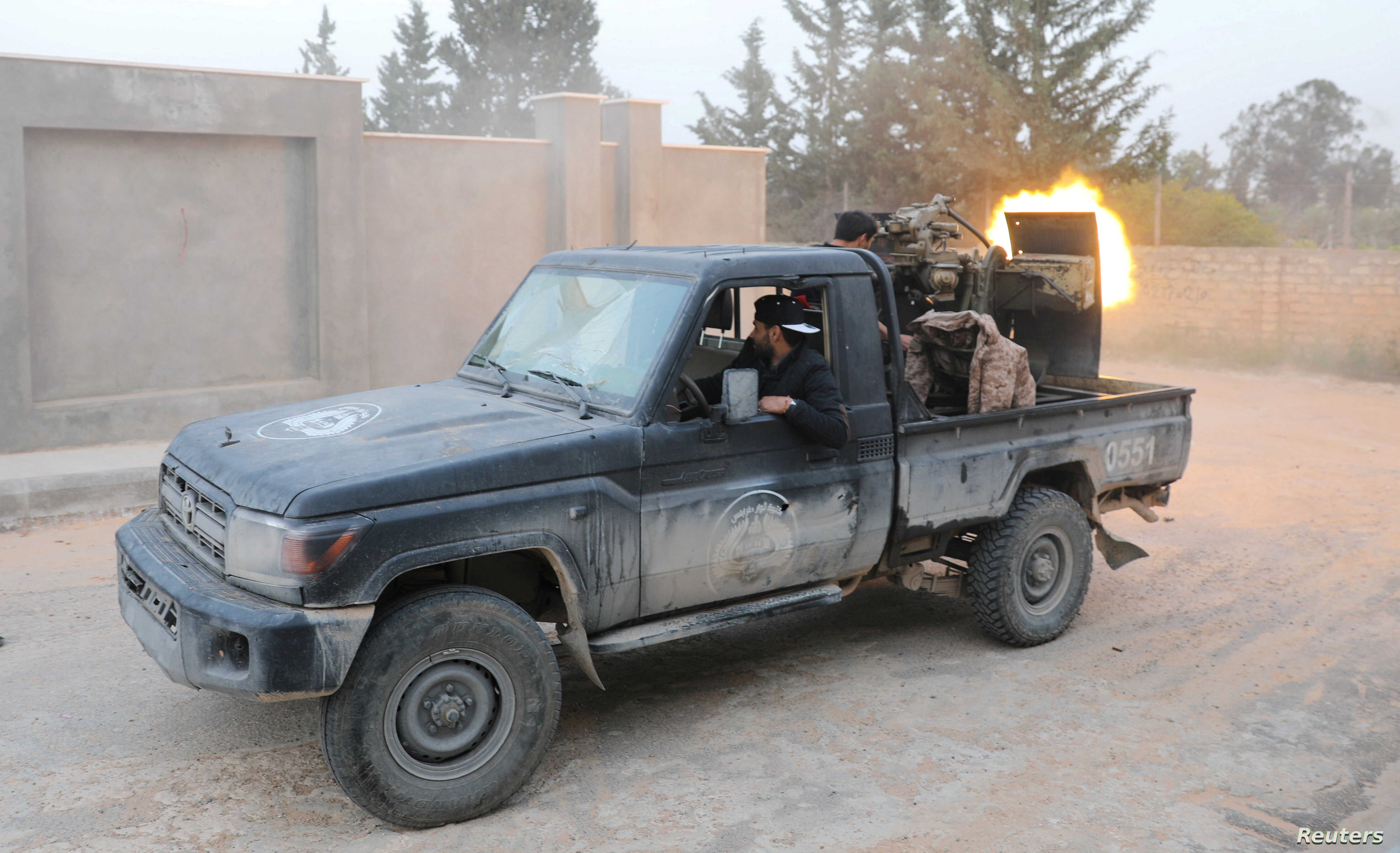 FILE - Members of the Libyan internationally recognized government forces fire during fighting with Eastern forces in Ain Zara in Tripoli, Libya, April 20, 2019.