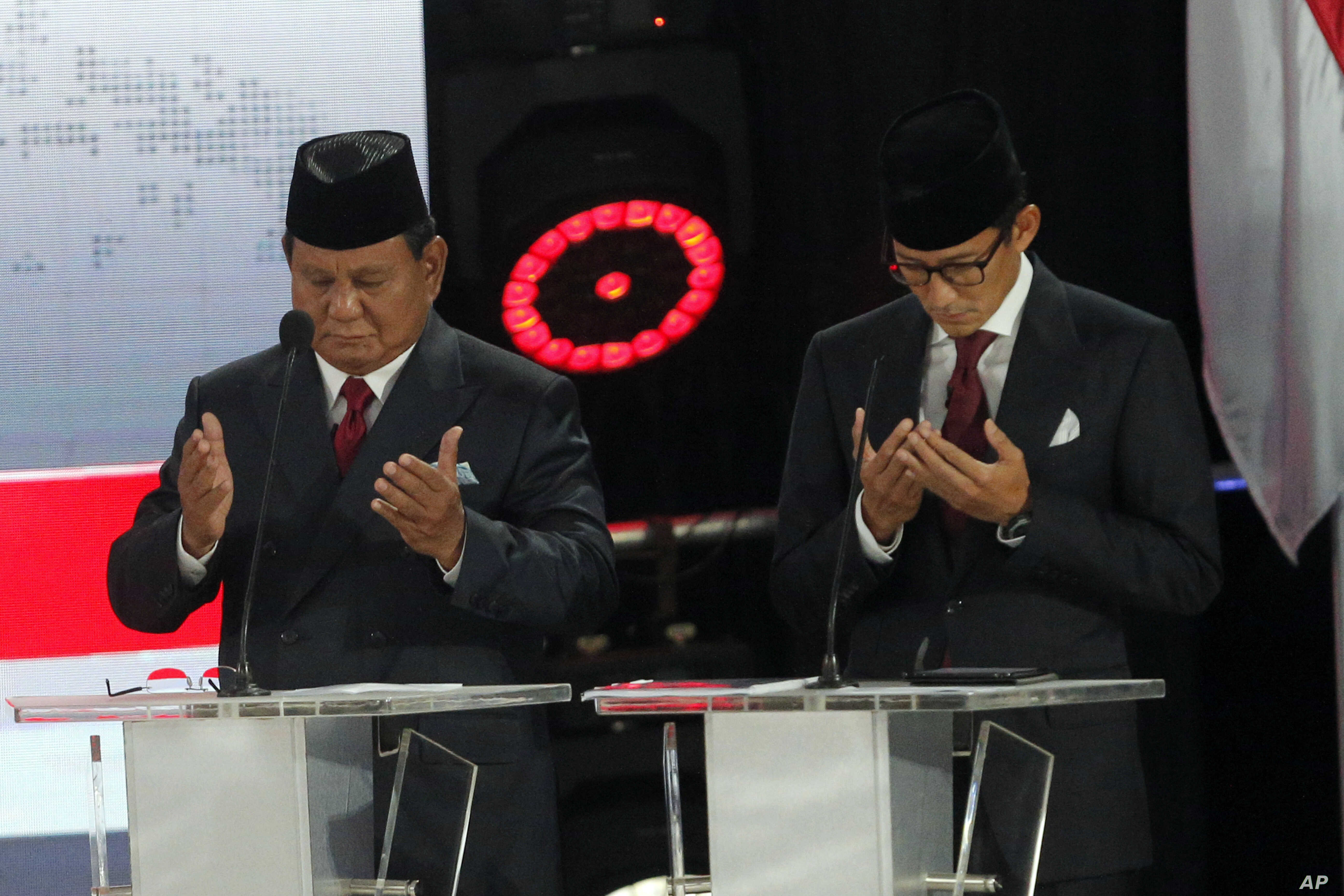 Indonesian presidential candidate Prabowo Subianto, left, with running mate Sandiaga Uno, prays prior to a televised presidential candidates debate in Jakarta, Indonesia, April 13, 2019.