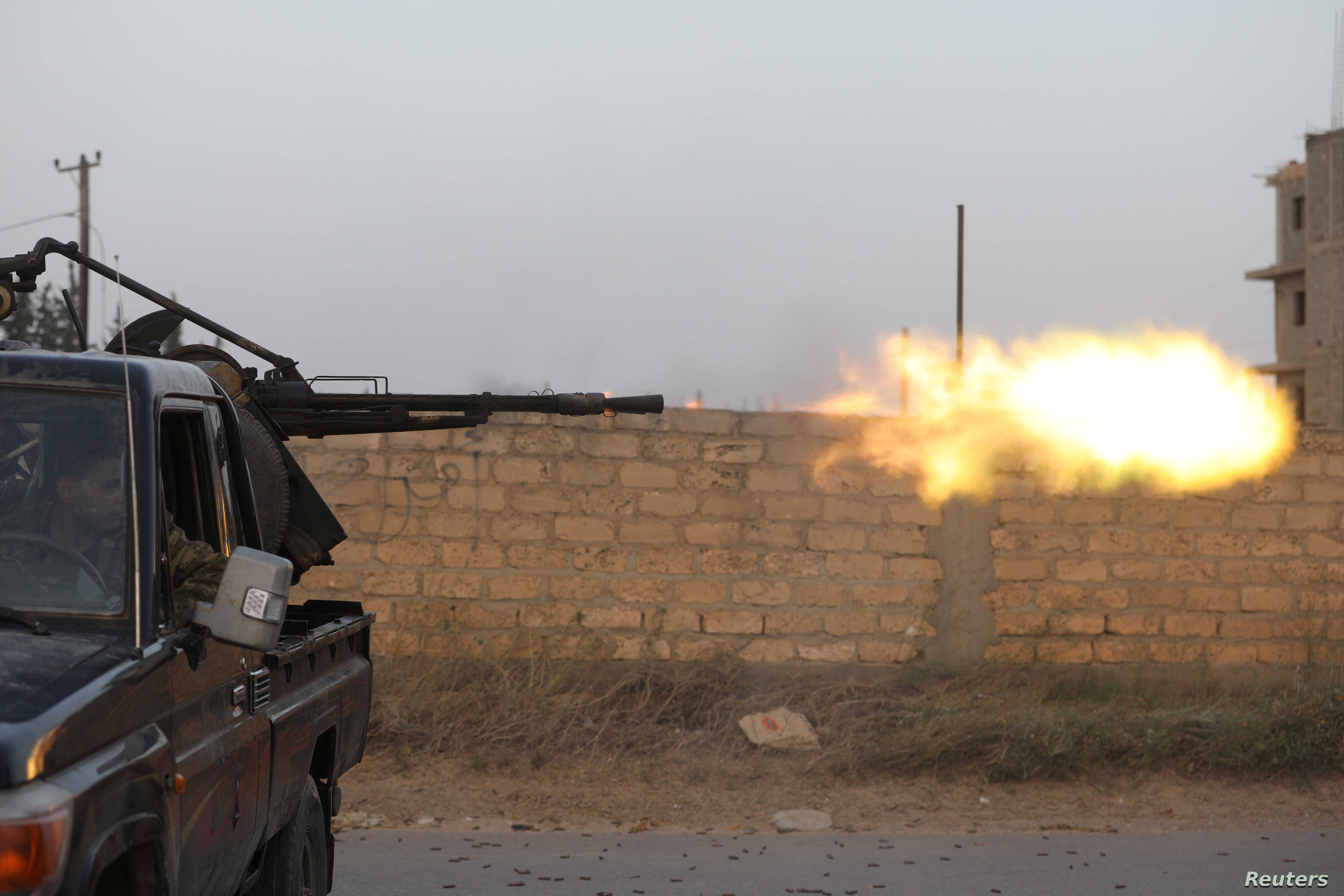 Members of the Libyan internationally recognized government forces fire during fighting with Eastern forces in Ain Zara, Tripoli, Libya, April 20, 2019.
