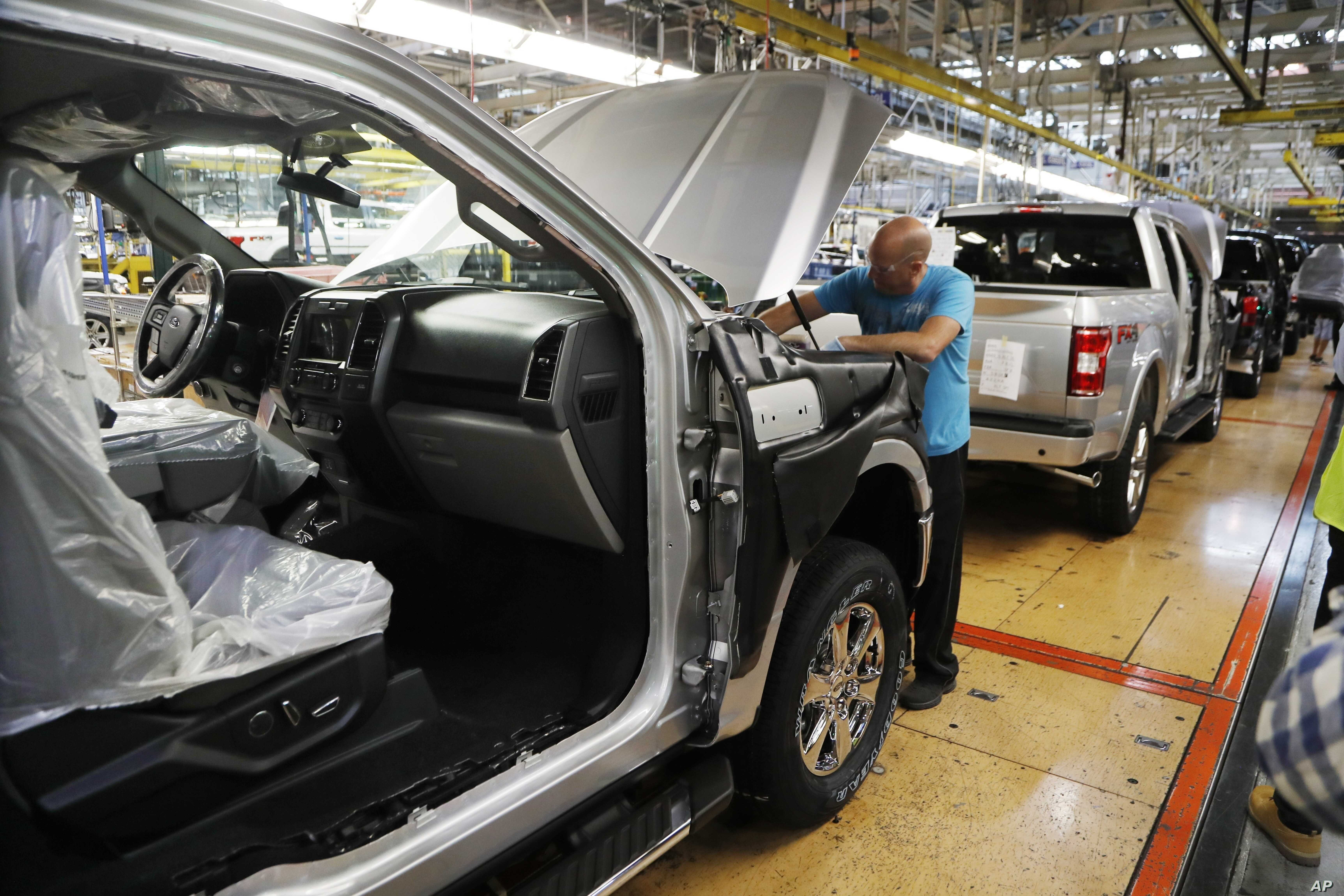 FILE- An assemblyman works on a Ford F-150 truck at the Ford Rouge plant in Dearborn, Mich., Sept. 27, 2018.