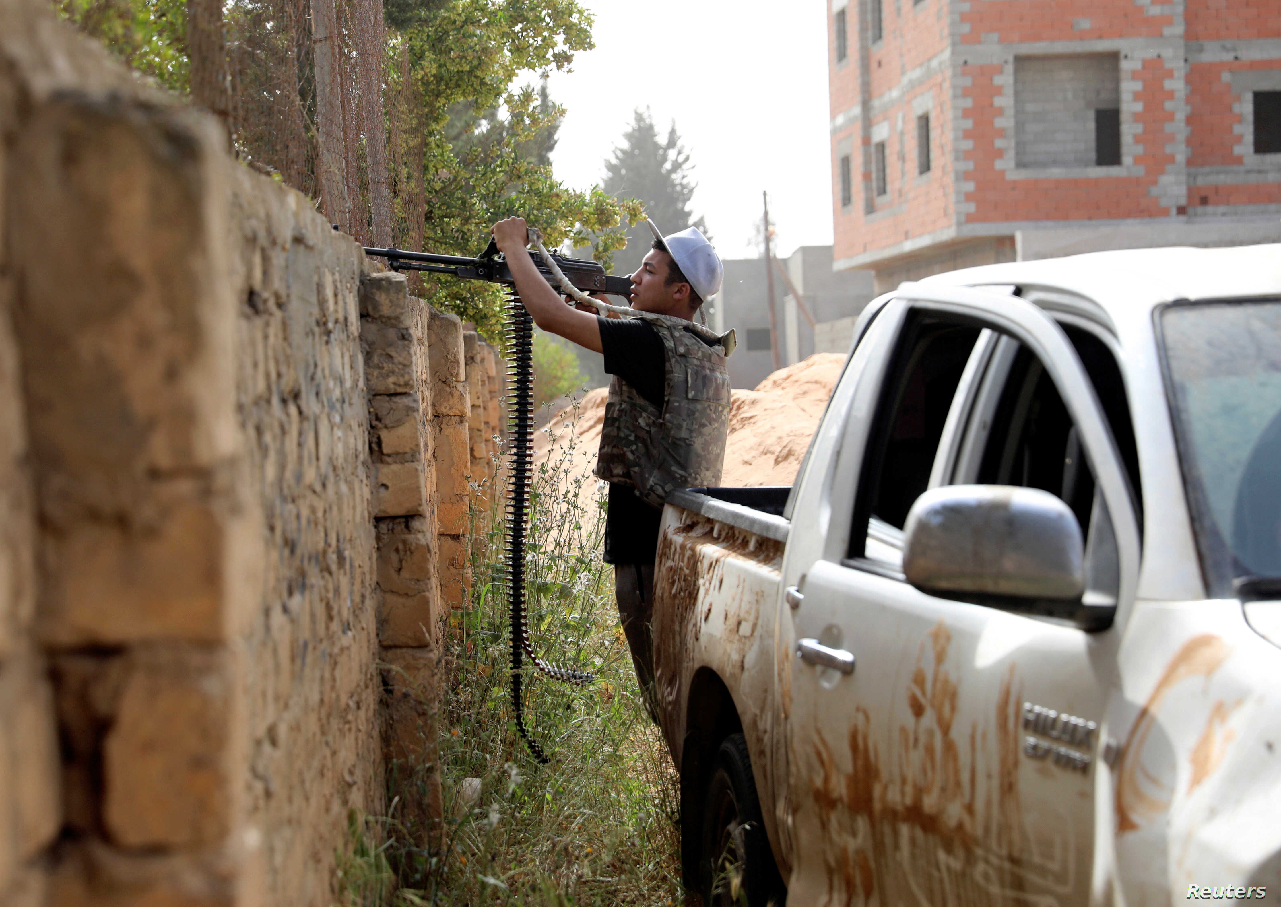 A member of the Libyan internationally recognized government forces fires at eastern forces in Ain Zara, Tripoli, Libya, April 25, 2019.