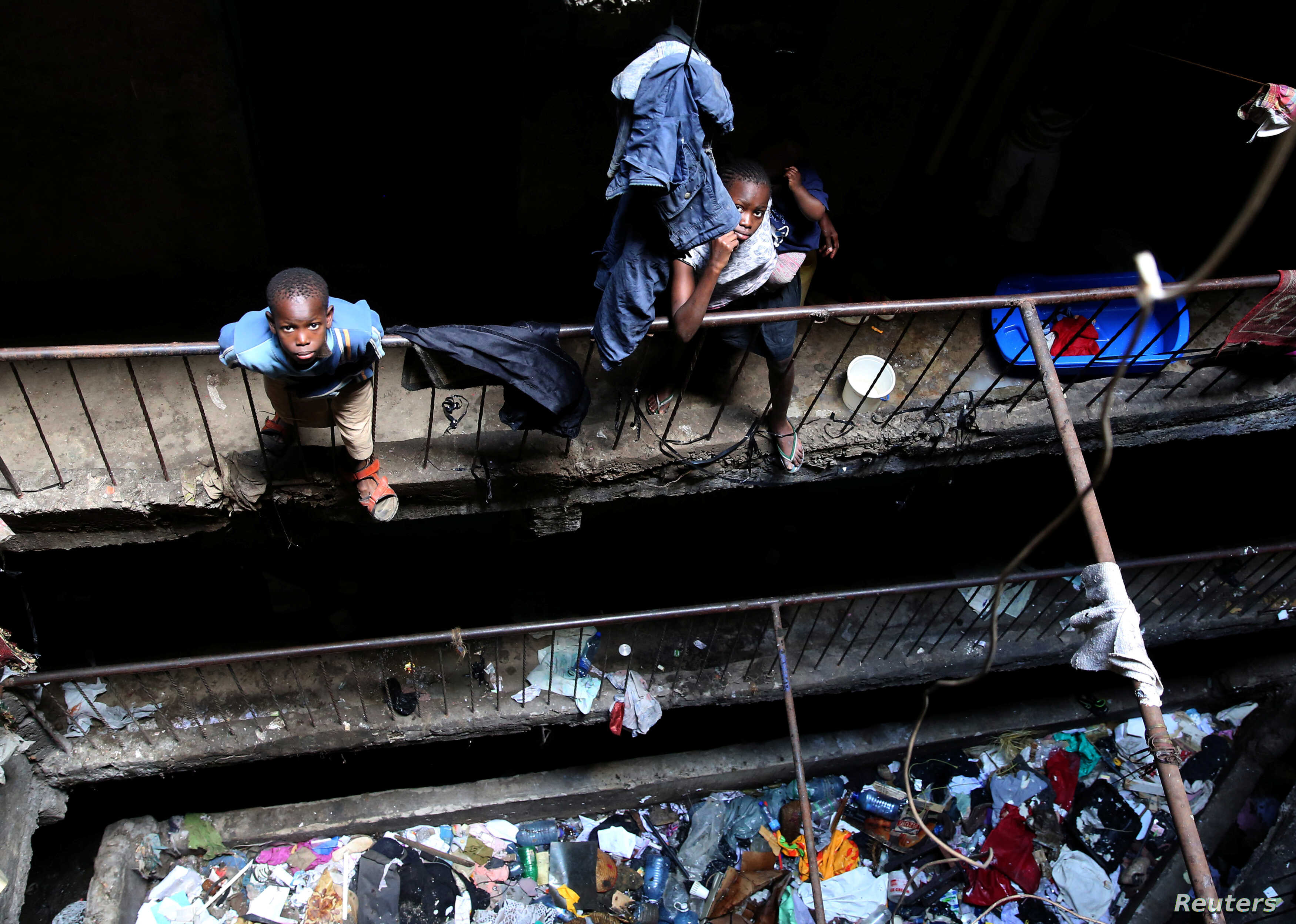 Children stand amid trash in a building earmarked for demolition in the Mathare neighborhood of Nairobi, Kenya, May 17, 2016.