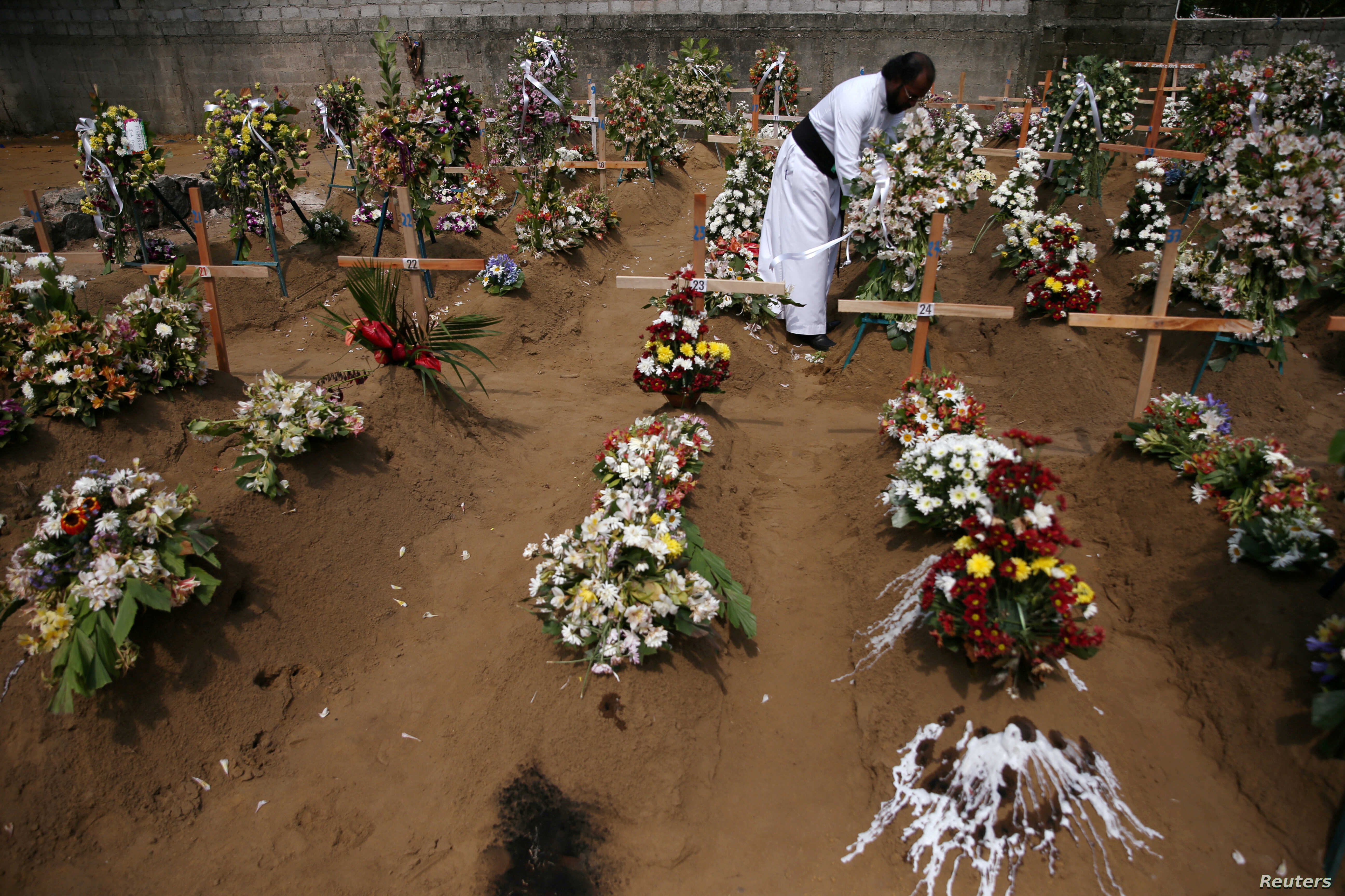 A priest arranges flowers at the site of a mass burial in Negombo, Sri Lanka, April 25, 2019.