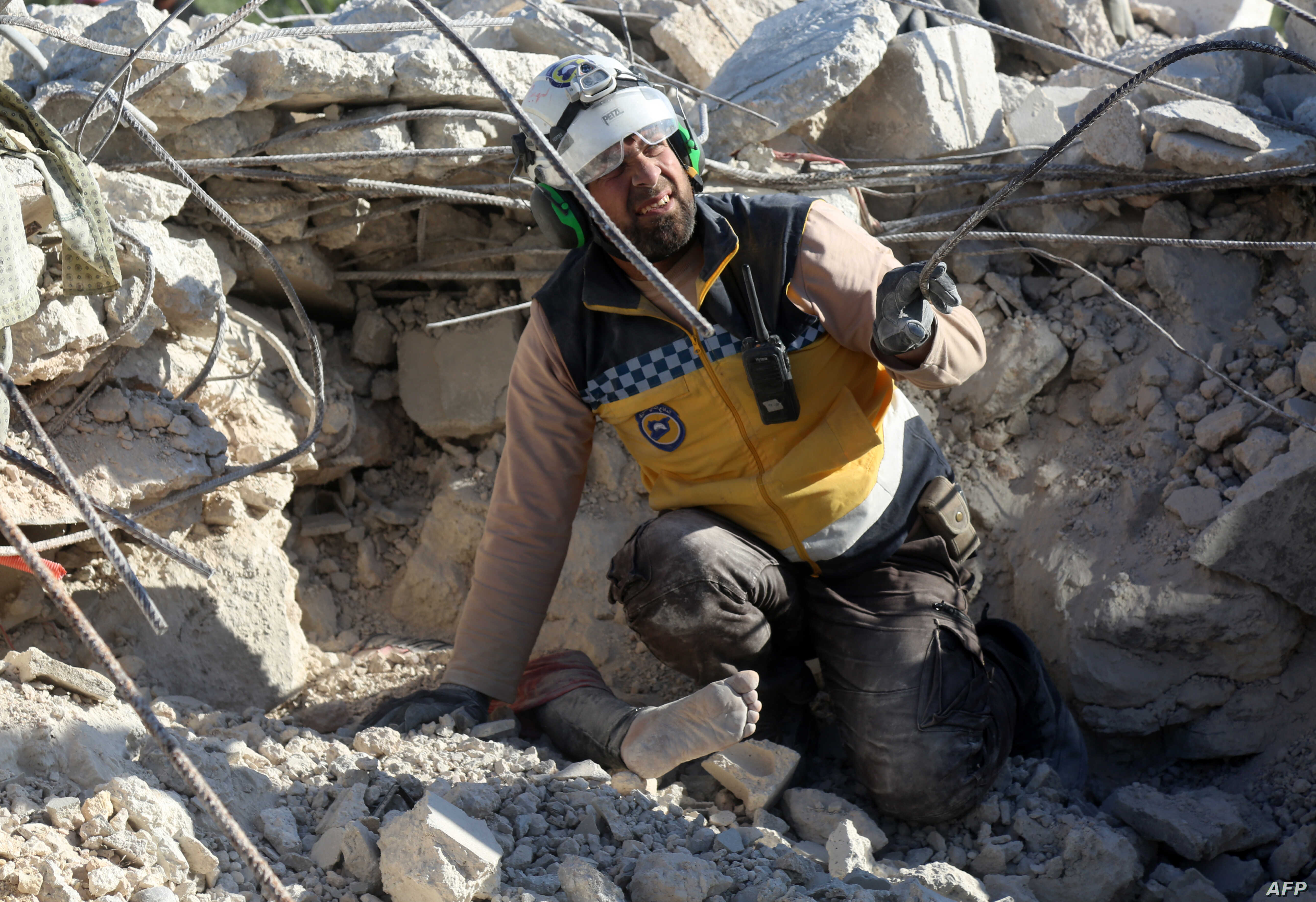 A member of the opposition Syrian Civil Defense reacts as he prepares to help remove the body of a woman buried under the rubble of a building, following shelling by government forces in the village of Rakaya Sijneh, Idlib province, Syria, May 4,2019...