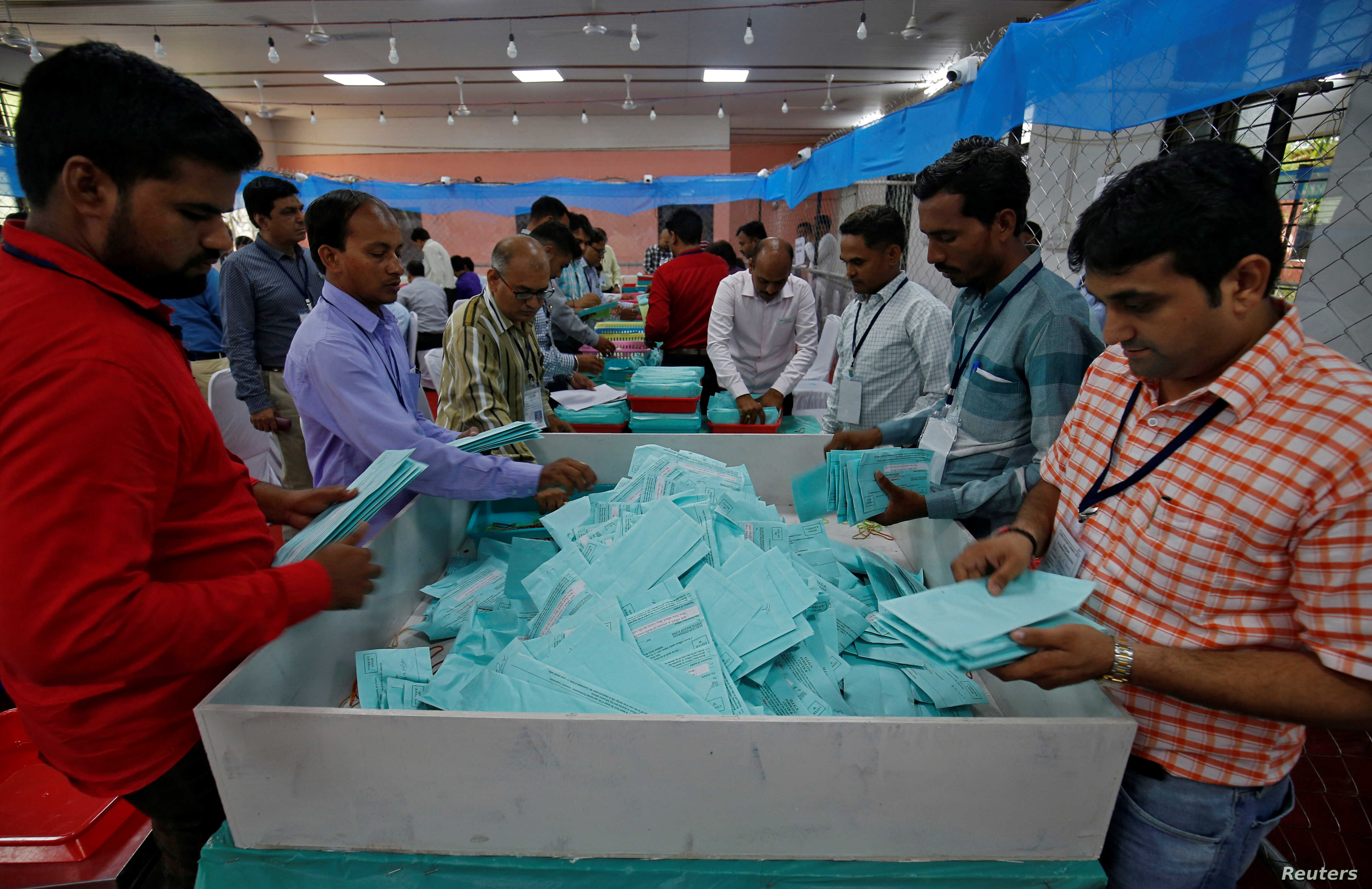 Election staff members sort ballot papers before counting them inside a vote counting center in Ahmedabad, India, May 23, 2019.