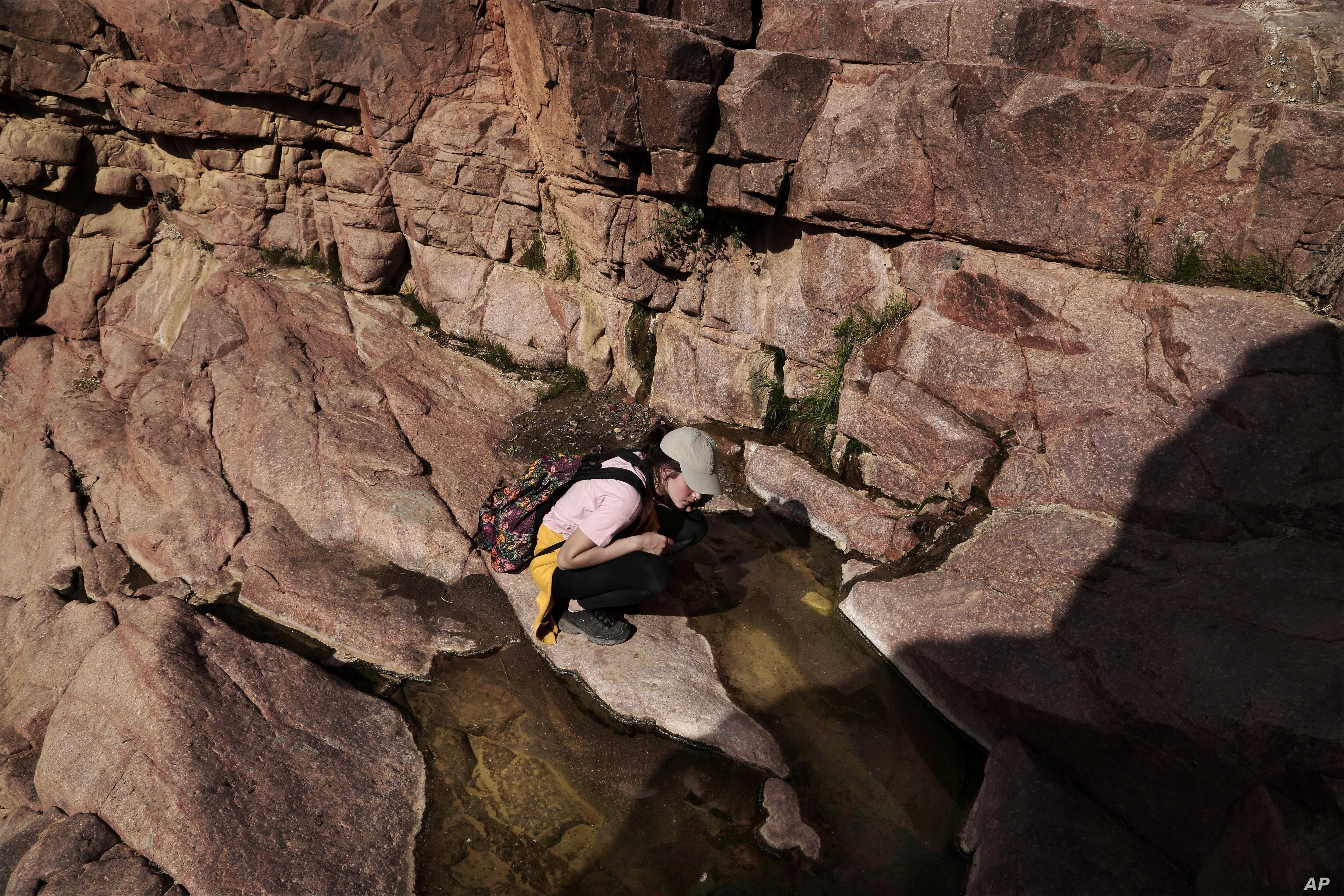 An Egyptian 21-year-old student on a trek looks at water remaining after a rainfall, in the mountains near Wadi Sahw, Abu Zenima, in South Sinai, Egypt, March 29, 2019.