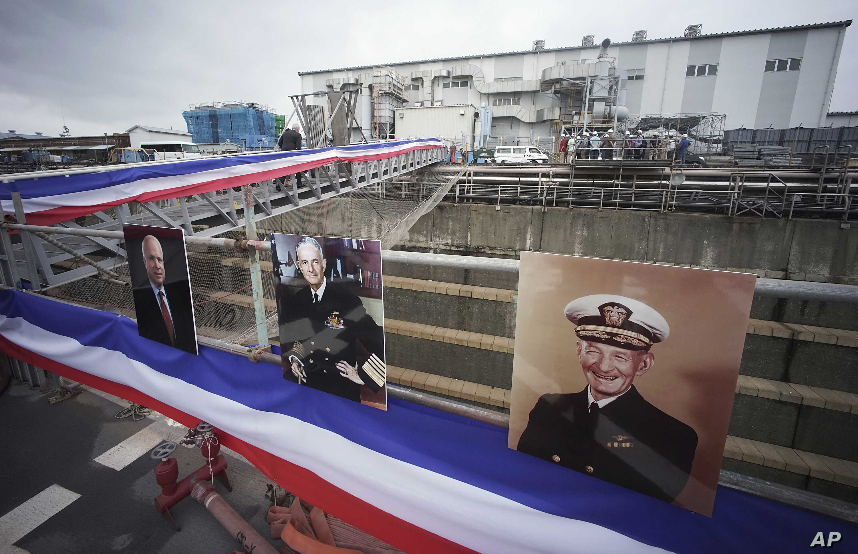 Near the portraits, from right, of  John S. McCain, John S. McCain, Jr. and John S. McCain III, Navy Secretary Richard Spencer and his wife Polly Spencer disembark from the USS John S. McCain after a rededication ceremony at the U.S. Naval base in Yo...