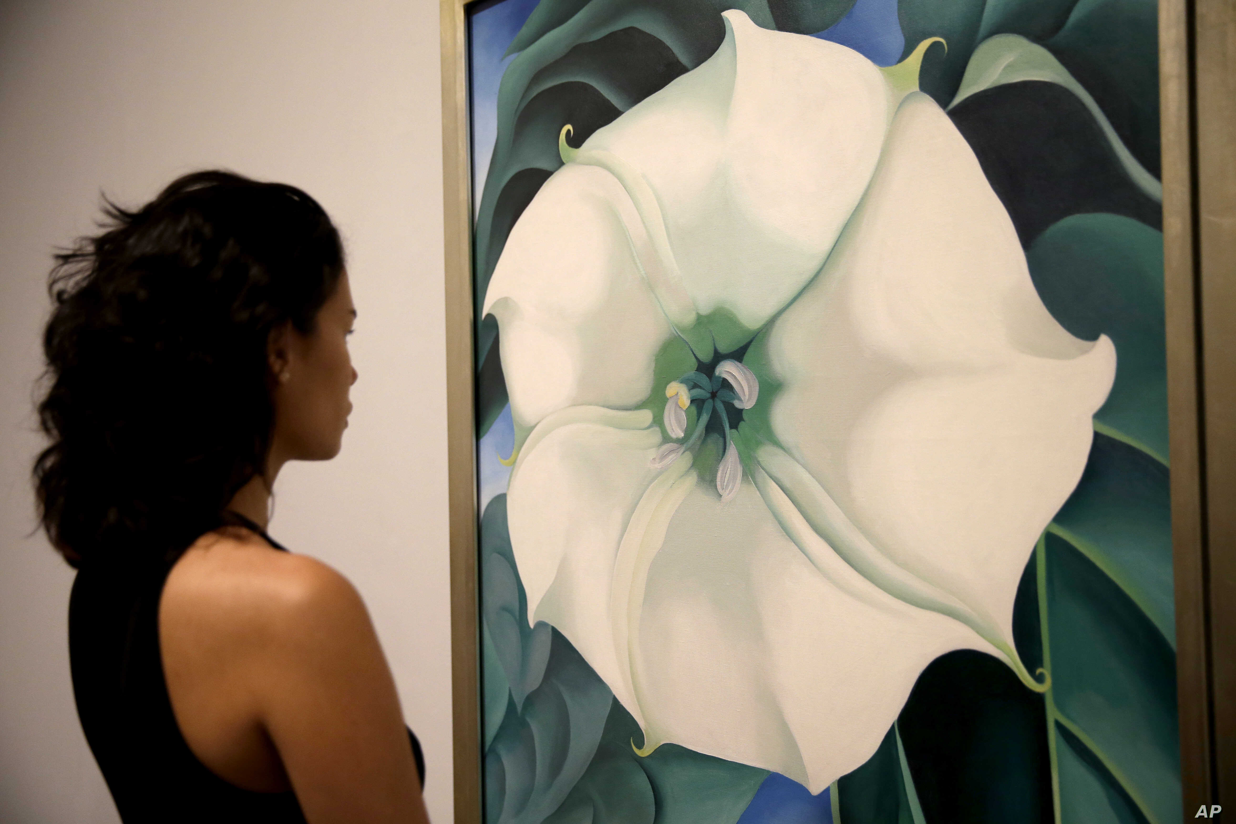 """A Tate Modern representative poses for photographs next to """"Jimson Weed/White Flower No.1"""" by American artist Georgia O'Keeffe at a press launch for her retrospective exhibition of over 100 works at the Tate Modern gallery in London, July 4, 2016."""