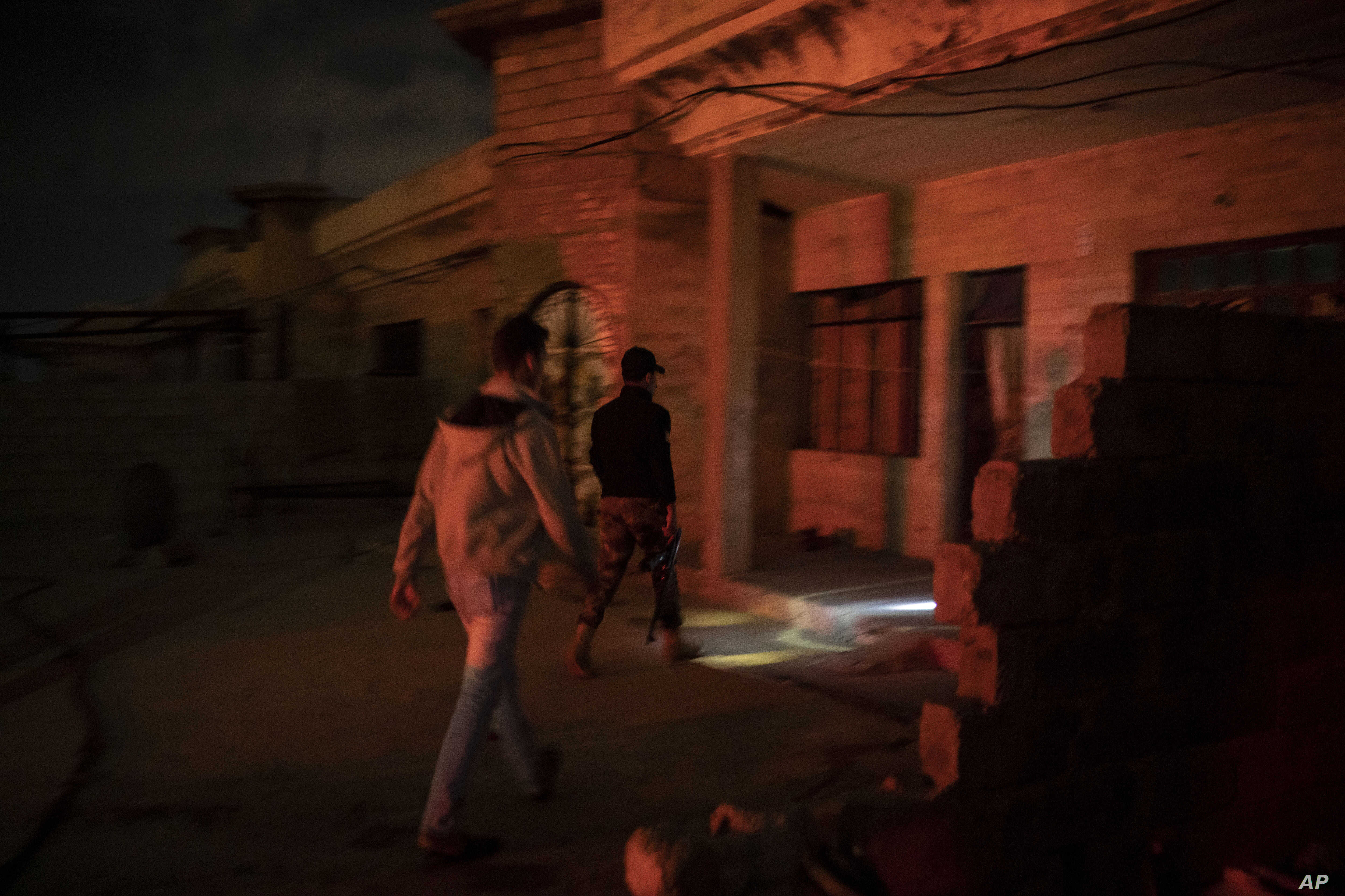 In this April 2, 2019 photo, an Iraqi army 20th division soldier walks with a civilian during a nighttime raid near Badoush, Iraq. The small town on the banks of the Tigris River was once one of the Islamic State group's most diehard strongholds.