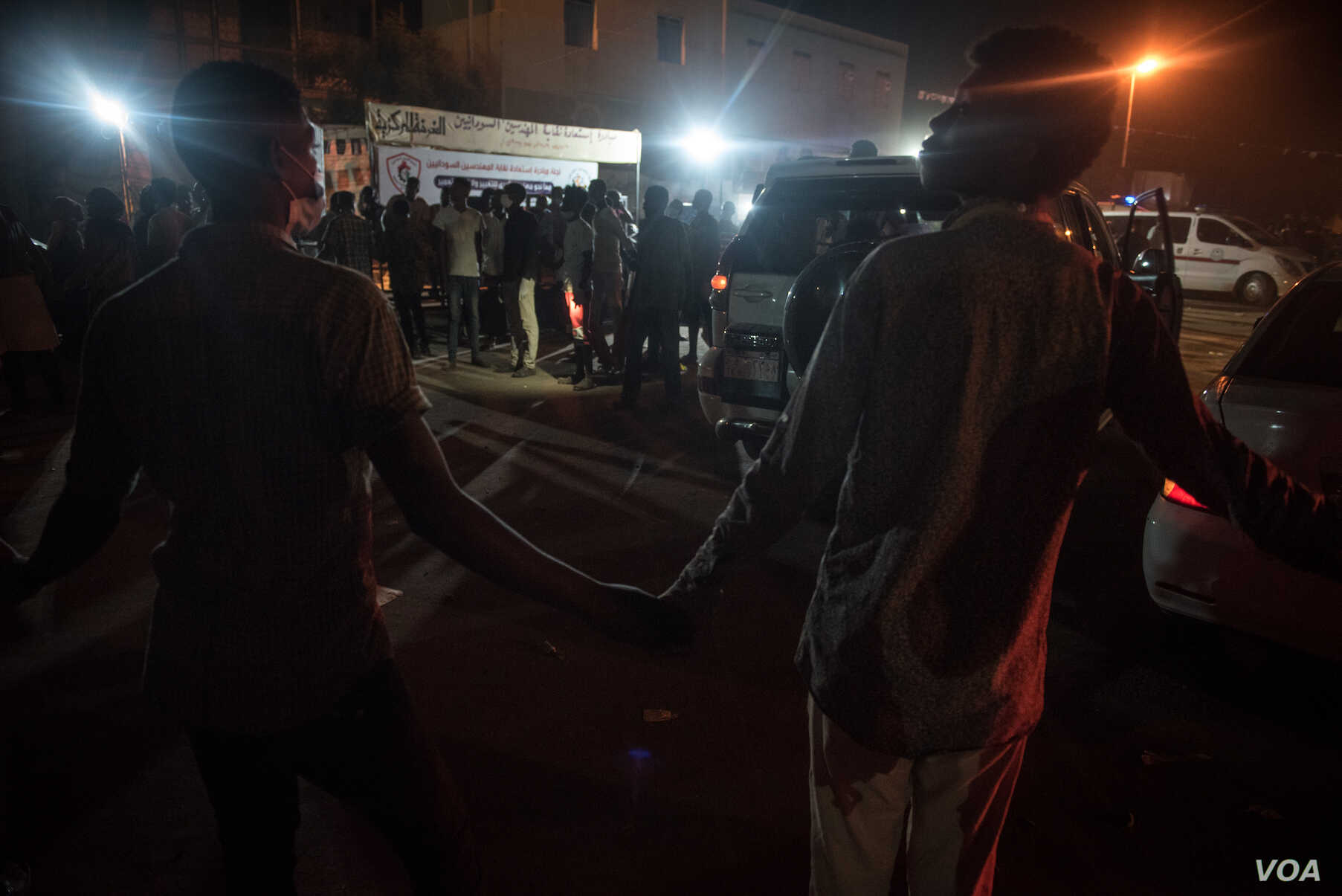 Protesters hold hands to create a cordon to create space for ambulances and other vehicles transporting wounded to hospital. (J. Patinkin for VOA)