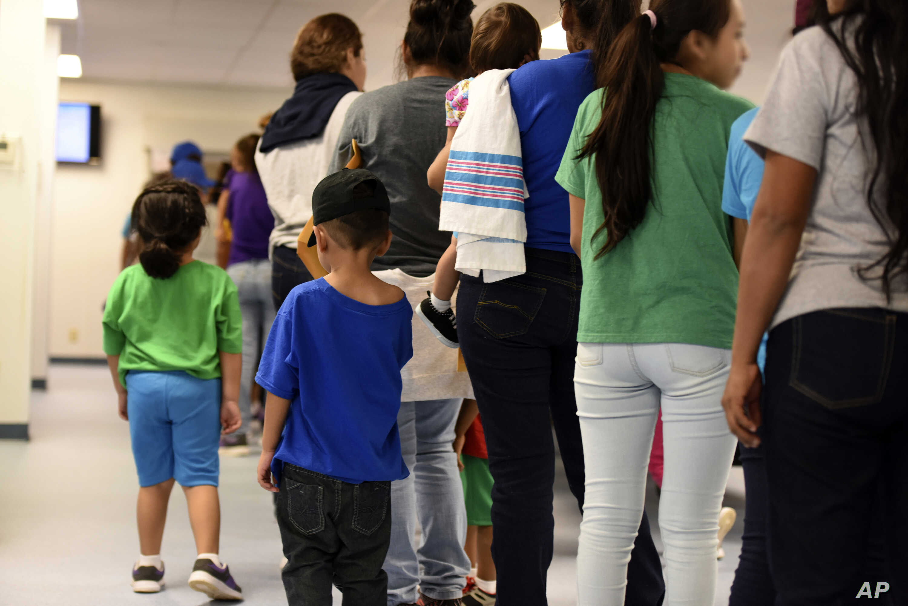 FILE - Mothers and children stand at South Texas Family Residential Center in Dilley, Texas, Aug. 9, 2018. Immigrant advocates are suing the U.S. government for allegedly detaining immigrant children too long and refusing to release them to family.