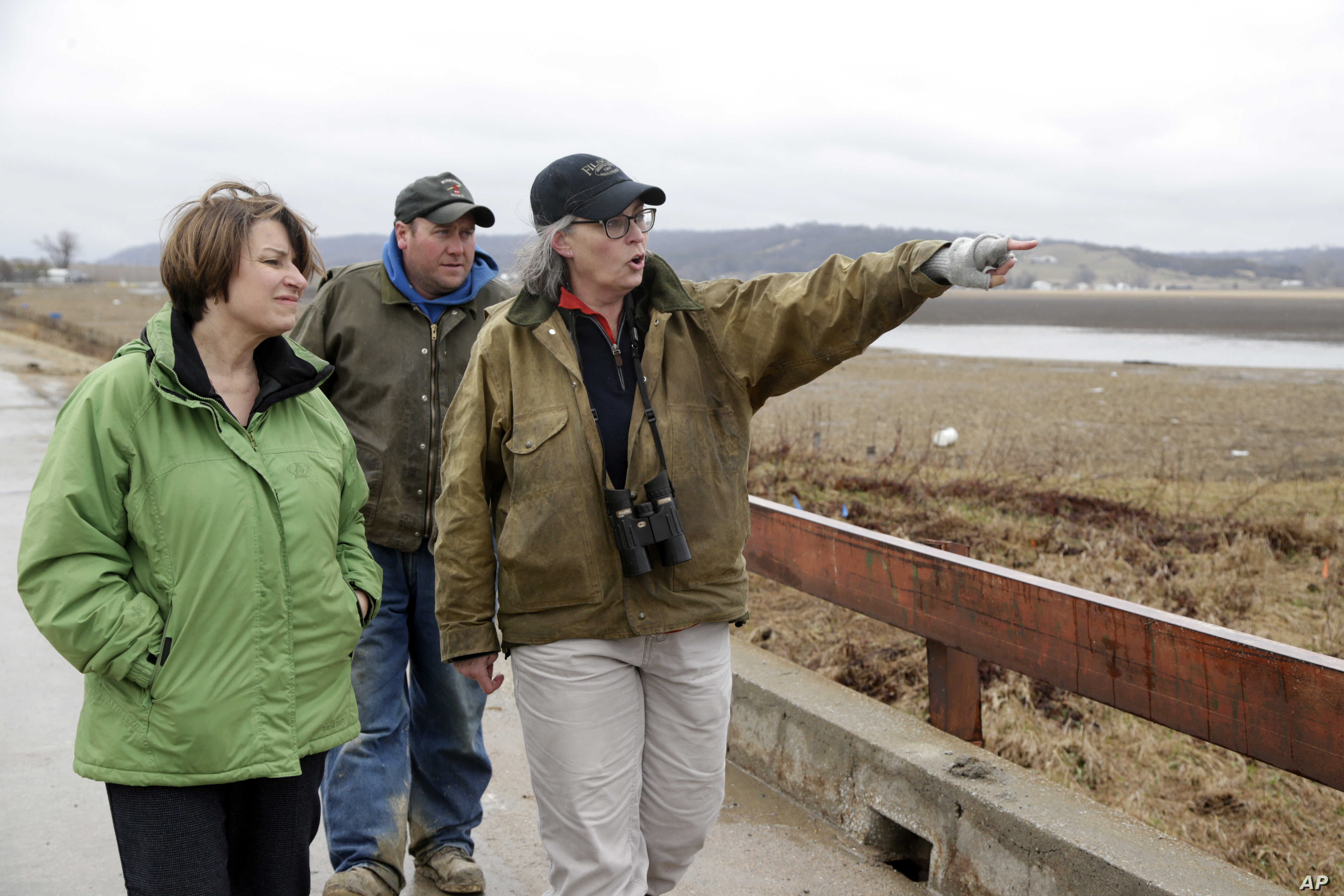 FILE - Local resident Fran Karr, right, with her husband Jason Karr, center, points out to Democratic presidential candidate Sen. Amy Klobuchar the location of their flooded home, of Pacific Junction, Iowa, Friday, March 29, 2019.