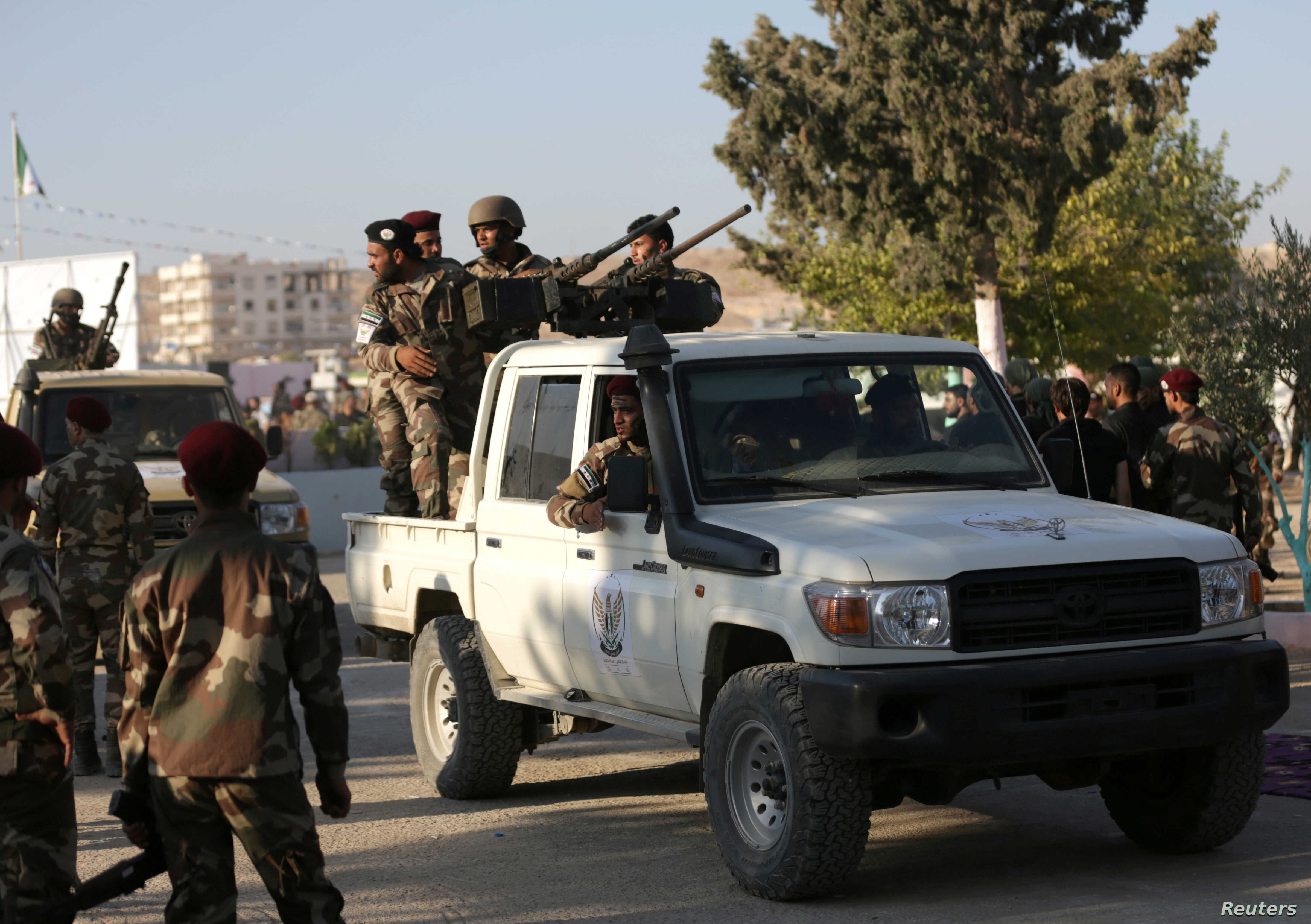 FILE - Fighters of National Army, backed by Turkey, stand at a back of a truck in the city of al-Bab, Syria, Aug. 5, 2018.