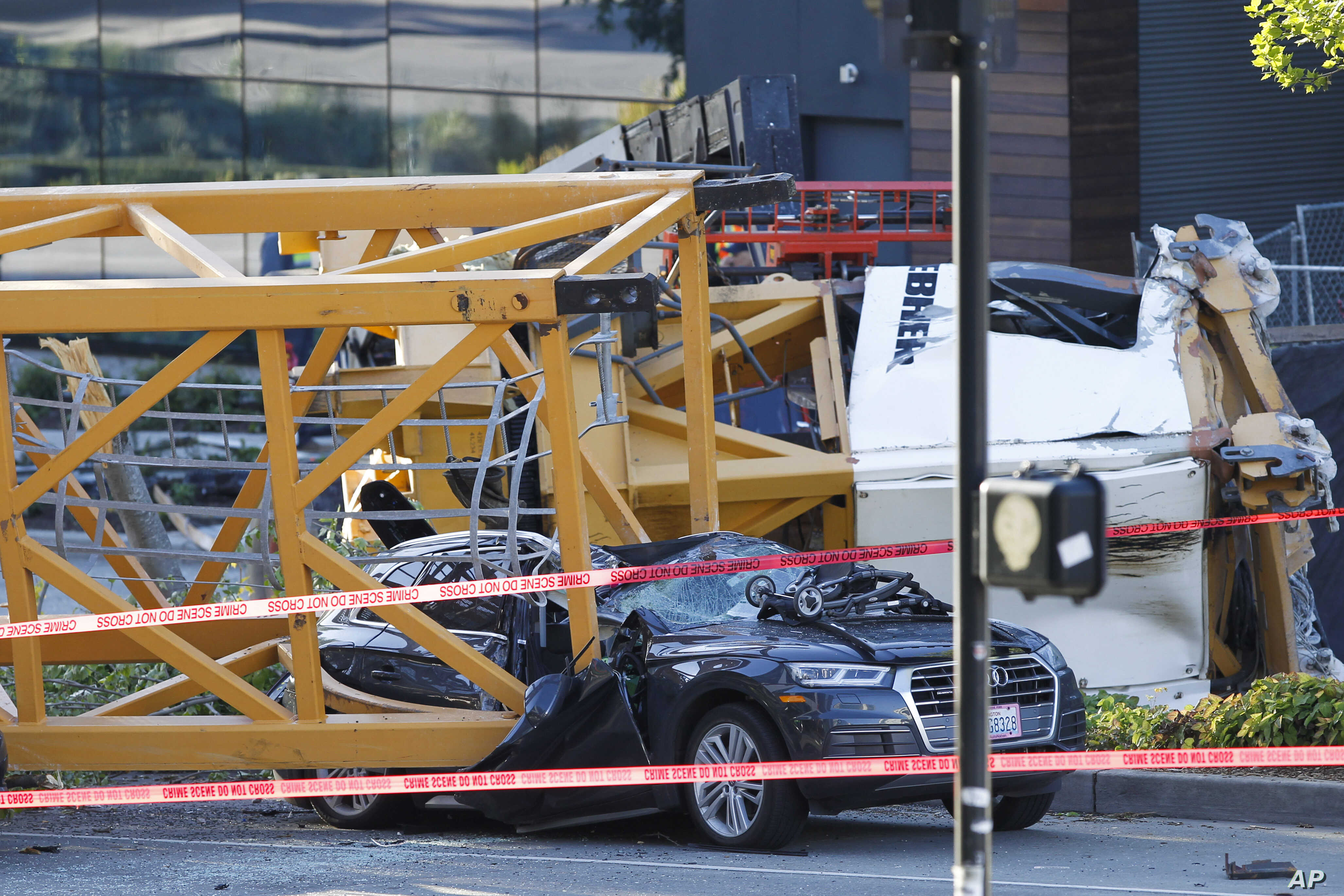Emergency crews work at the scene of a construction crane collapse, April 27, 2019. The crane collapsed near the intersection of Mercer Street and Fairview Avenue pinning cars underneath it near Interstate 5.