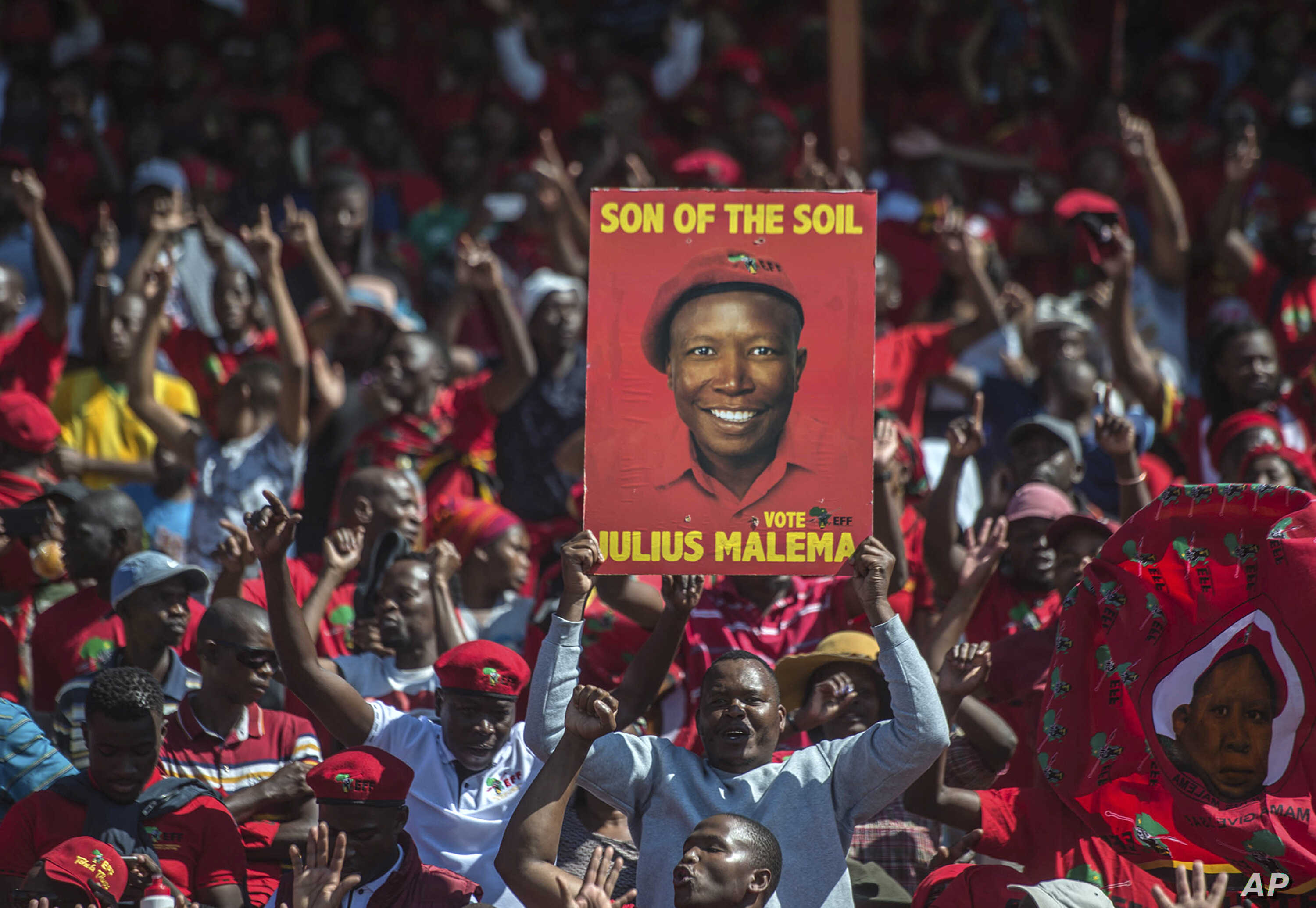 Supporters of the Economic Freedom Fighters (EFF) party hold up an election poster of leader Julius Malema during a May Day Rally in Alexandra Township, Johannesburg, May 1, 2019.