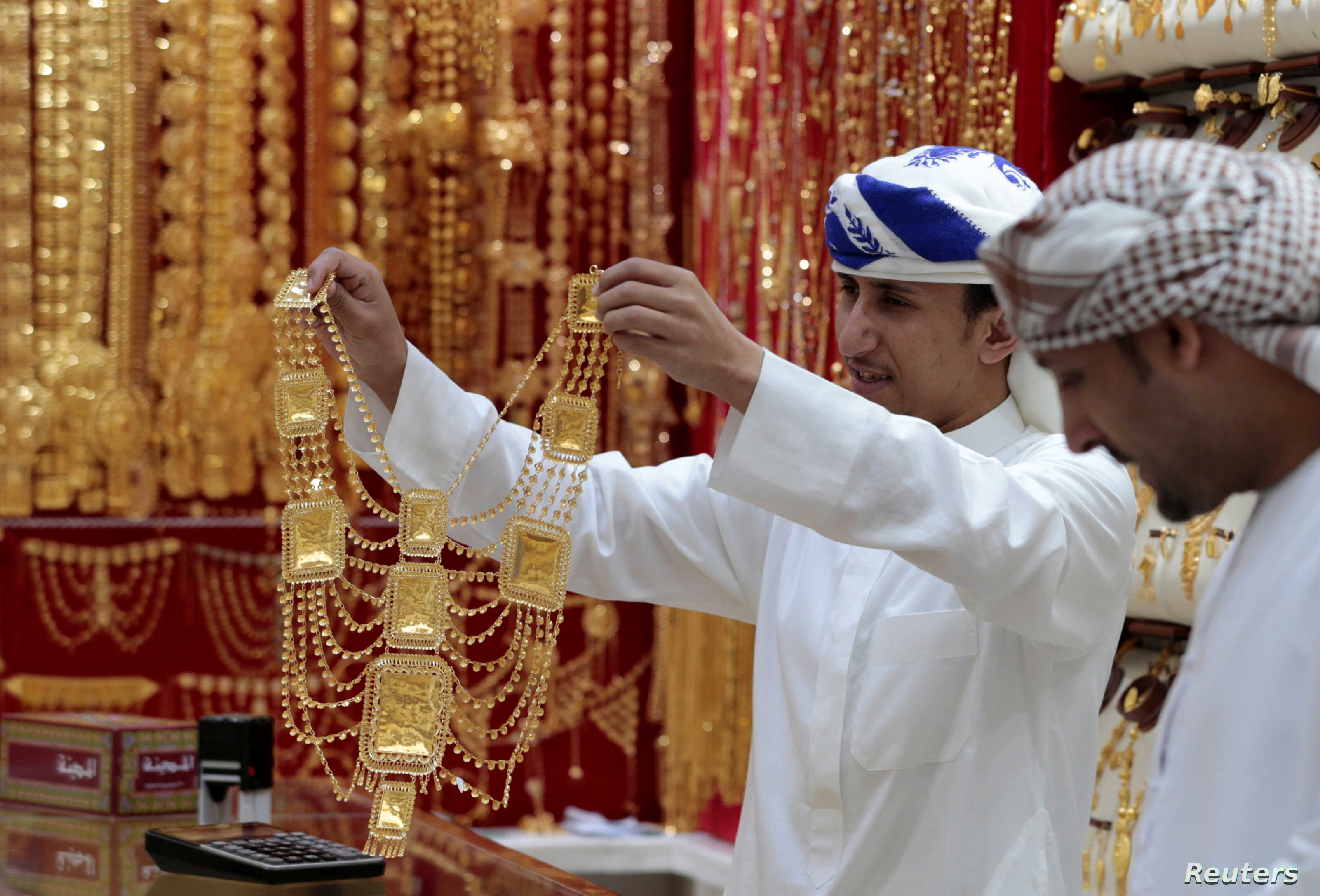 An employee shows a customer gold jewellery in a shop at the Gold Souq in Dubai, United Arab Emirates, March 24, 2018.
