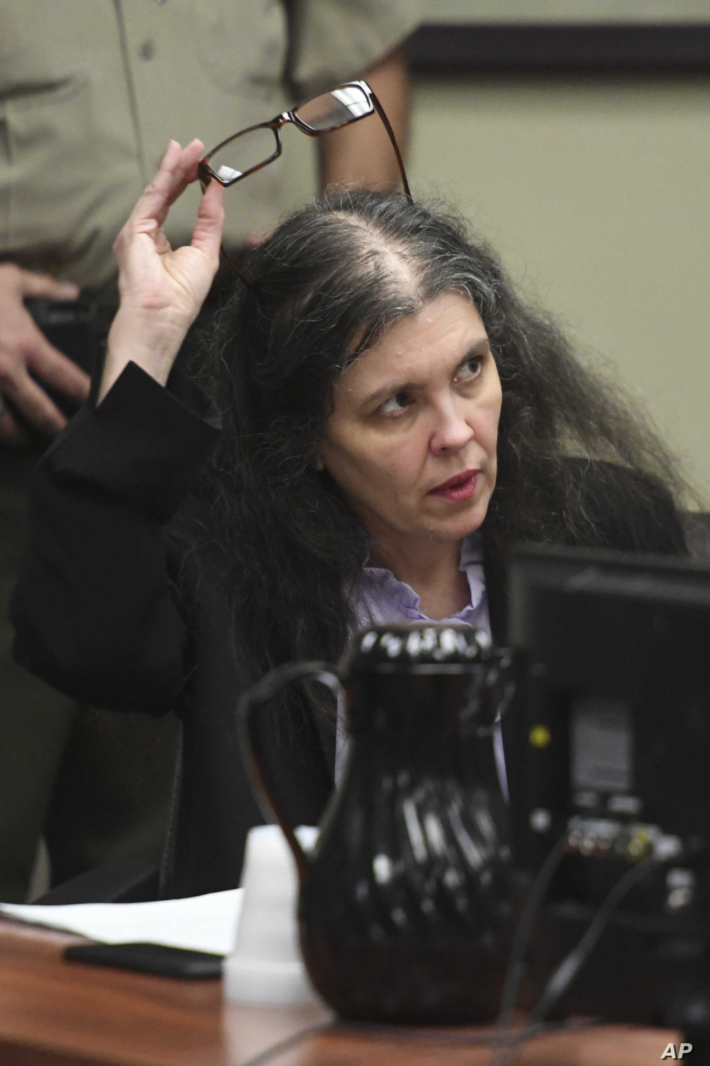 Louise Turpin listens to her attorney during a sentencing hearing, April 19, 2019, in Riverside, Calif. Turpin and her husband, David, pleaded guilty of neglect and abuse of 12 of their 13 children.