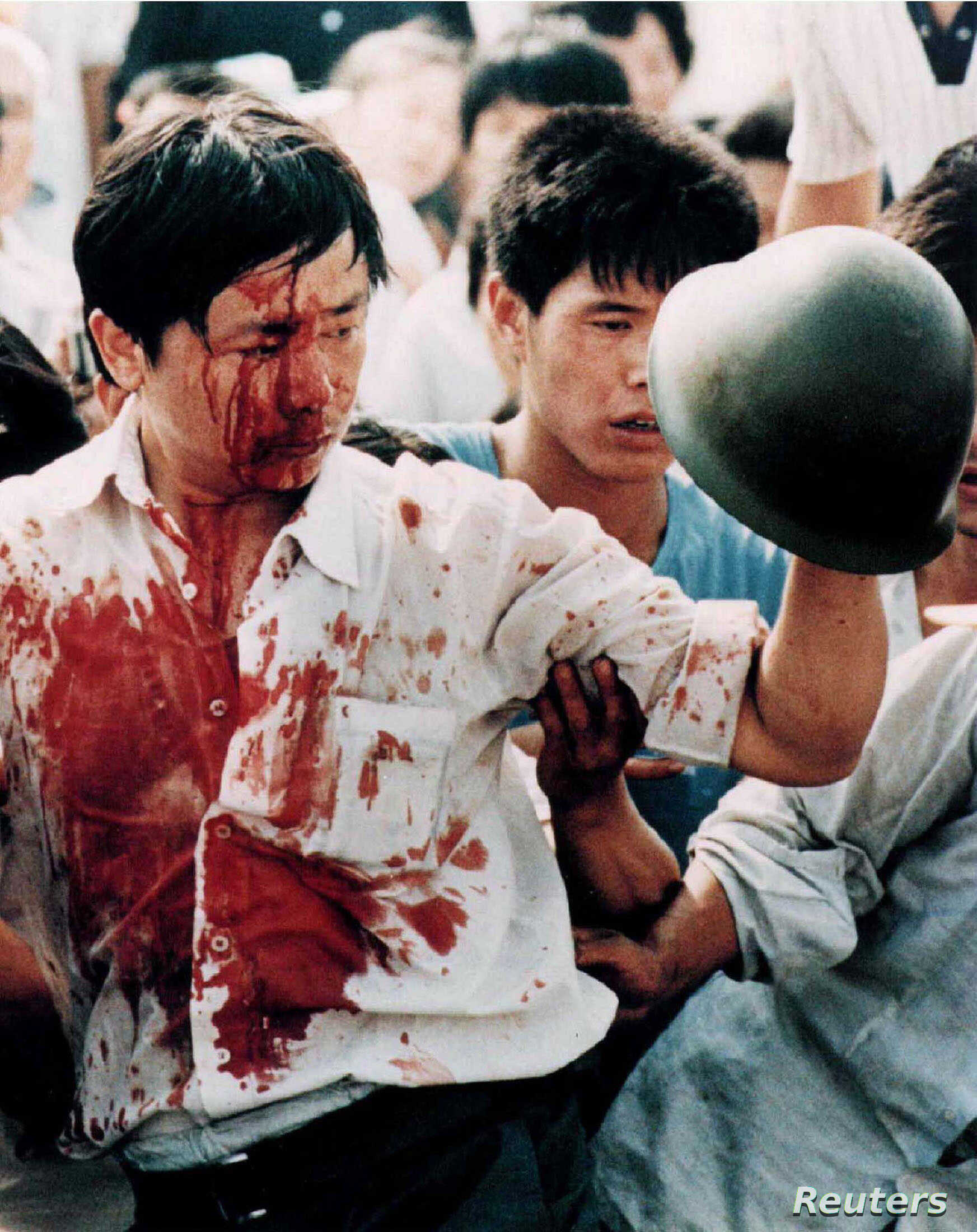 FILE - A blood-covered protester holds a Chinese soldier's helmet following violent clashes with military forces during the 1989 pro-democracy demonstrations in Beijing's Tiananmen Square in this June 4, 1989 photo.
