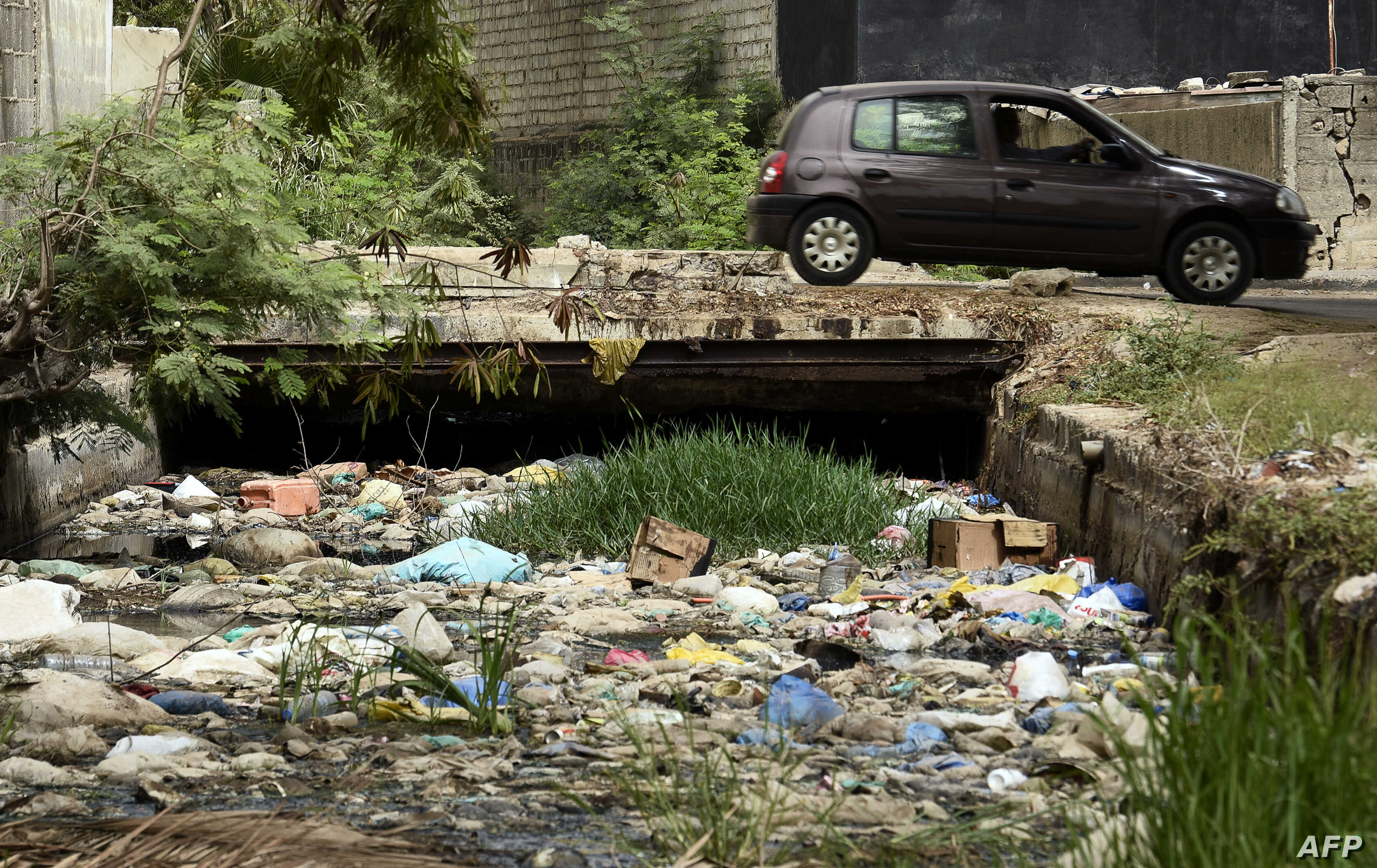 FILE - A car passes by a canal full with trash in Dakar, June 2, 2018.