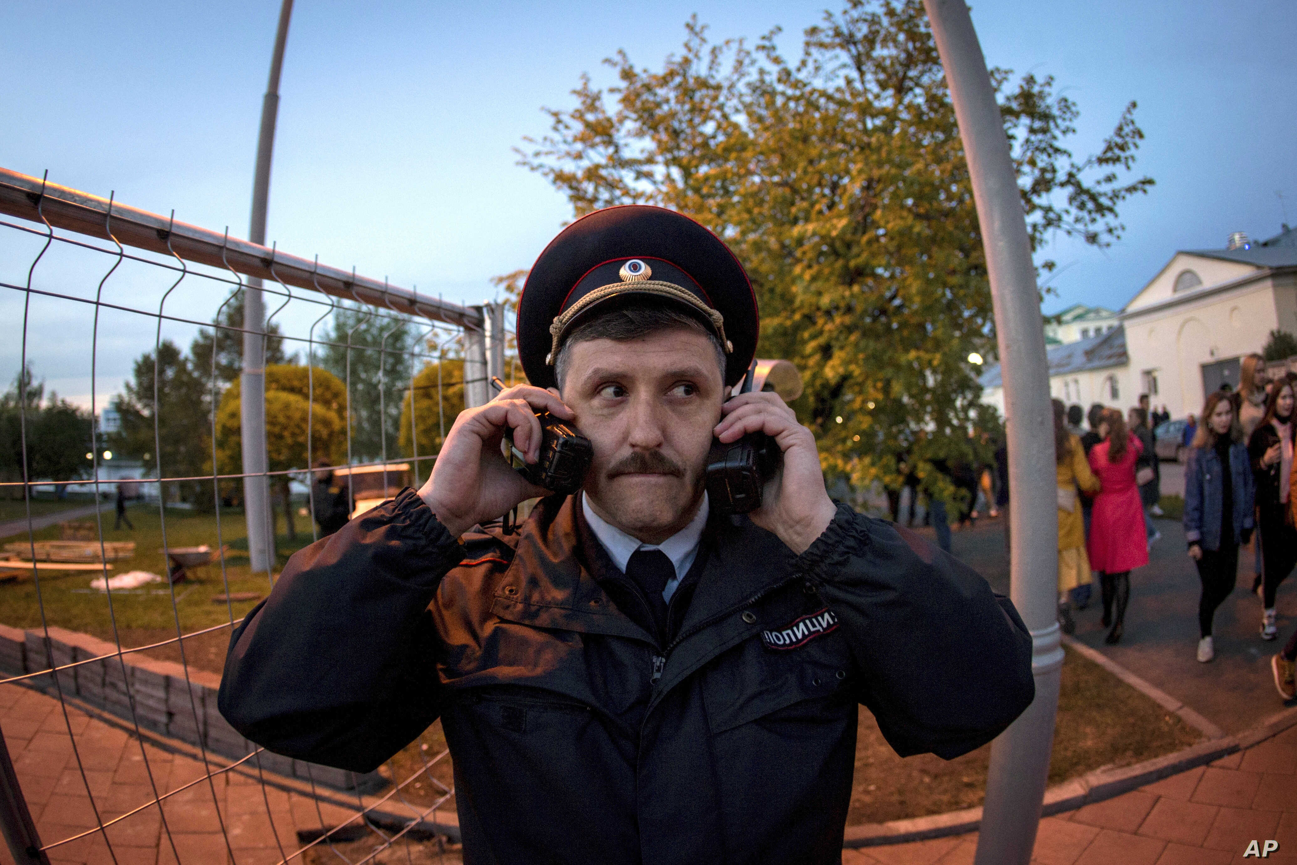 A police officer speaks on two walkie-talkies as demonstrators gather ahead of a protest against plans to construct a cathedral in a park in Yekaterinburg, Russia, May 15, 2019.